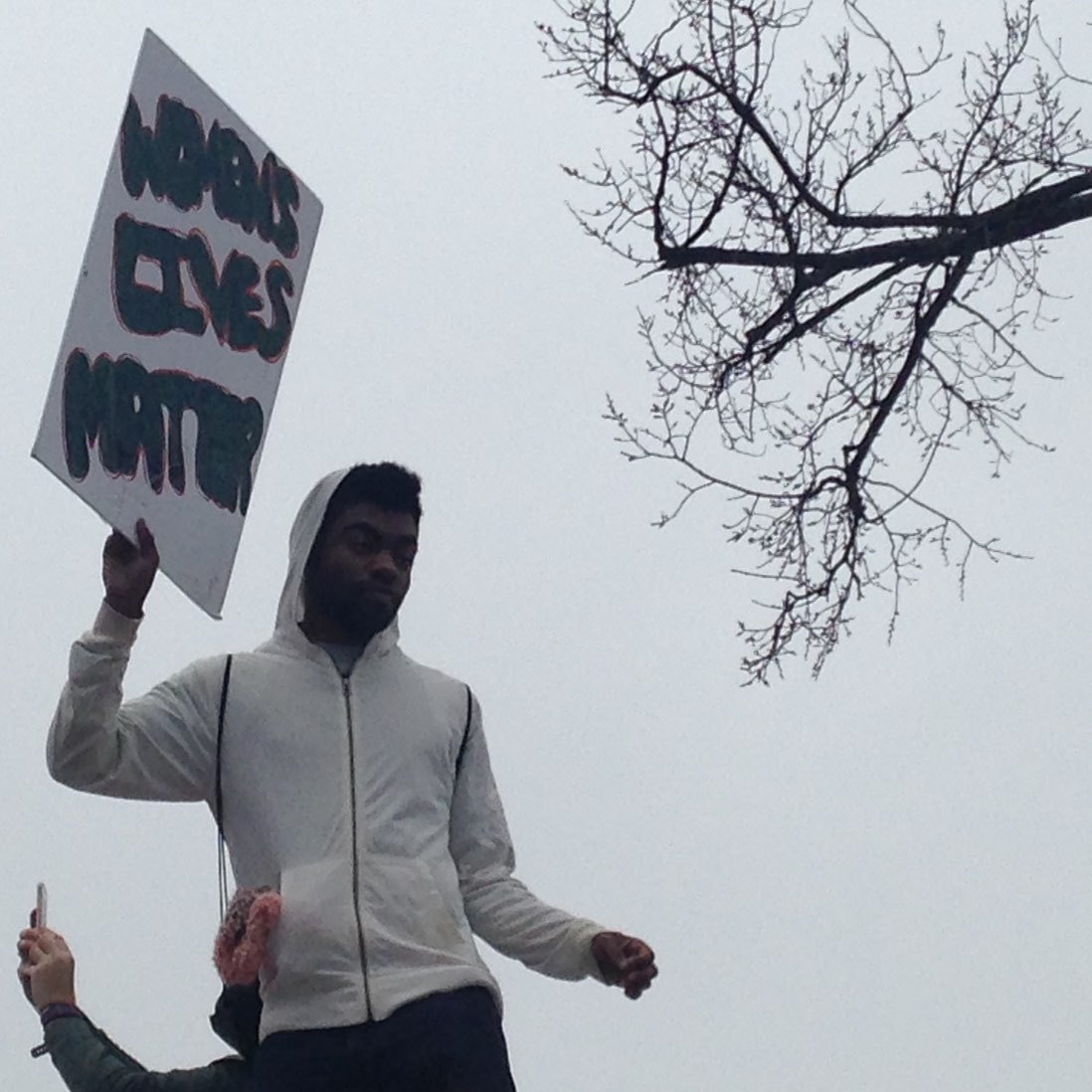 A young black man holds up a sign that says Women's lives matter.