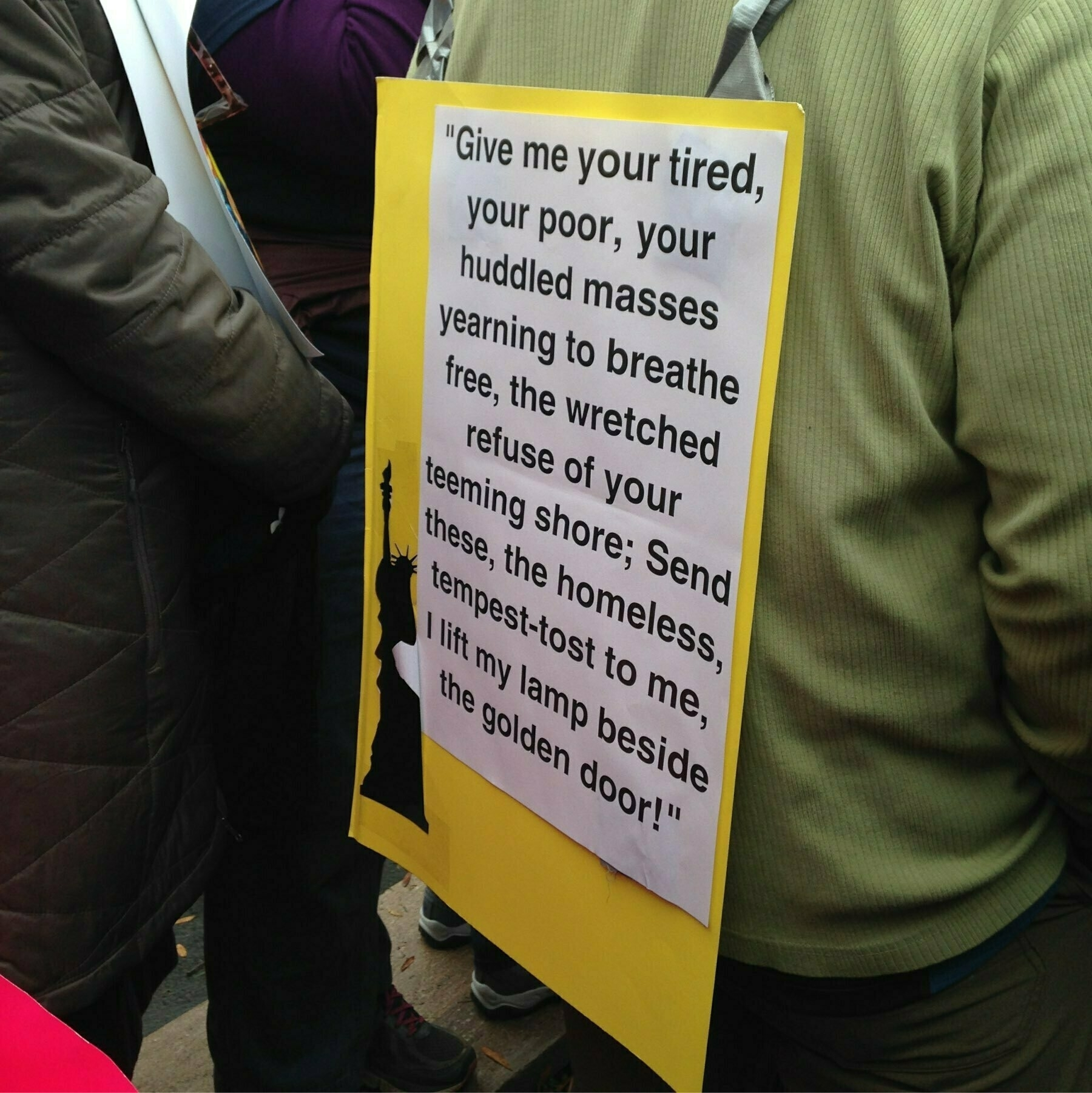 """A man wears a paper sign with the inscription from the Statue of Liberty """"Give me your tired, your poor, your huddled masses yearning to be free..."""""""