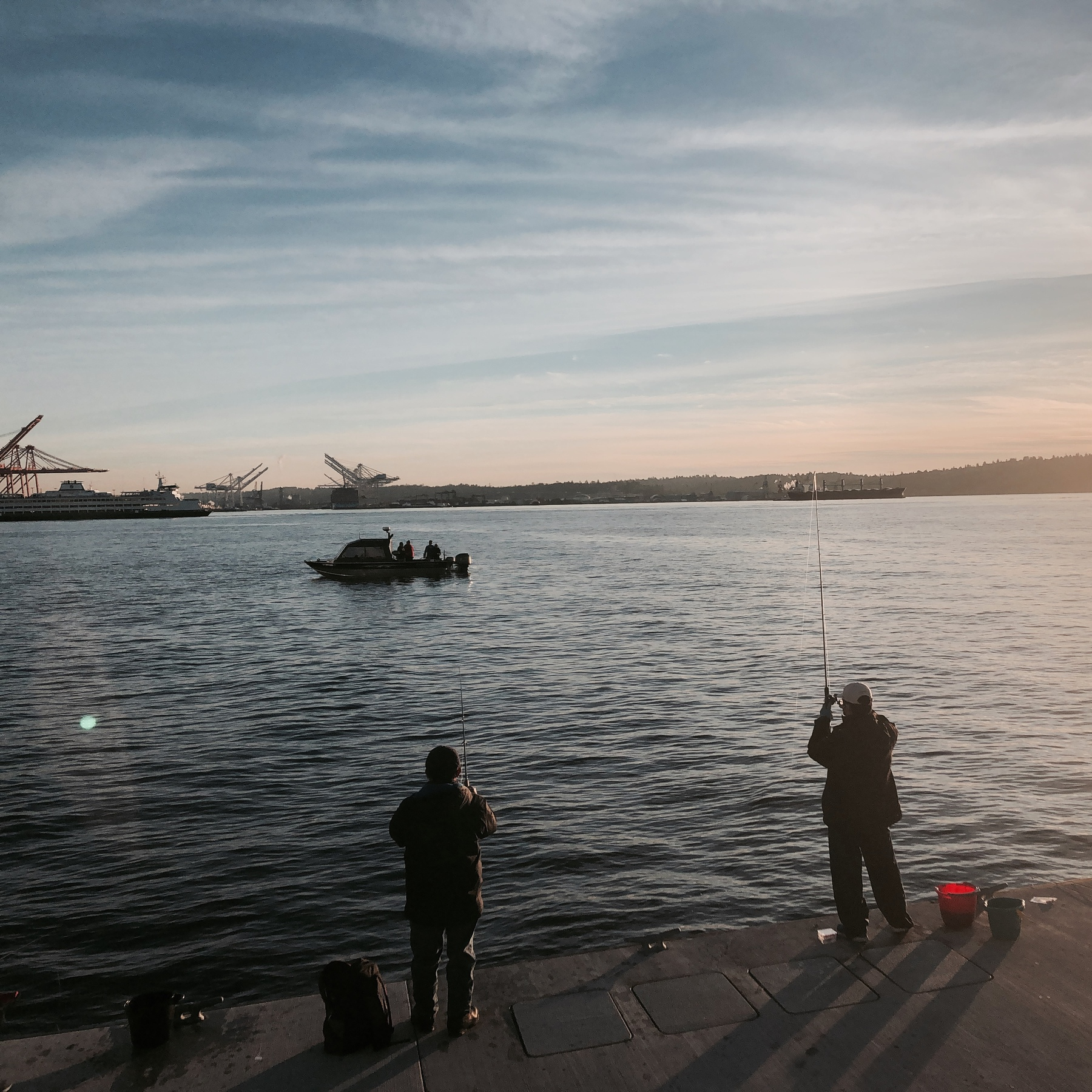 Two men fish on a concrete pier. A small boat out on the bay has fishermen in the back.