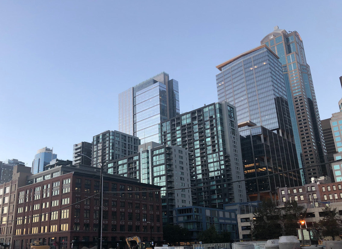 blocky steel and glass buildings reflect the light of the sunset.