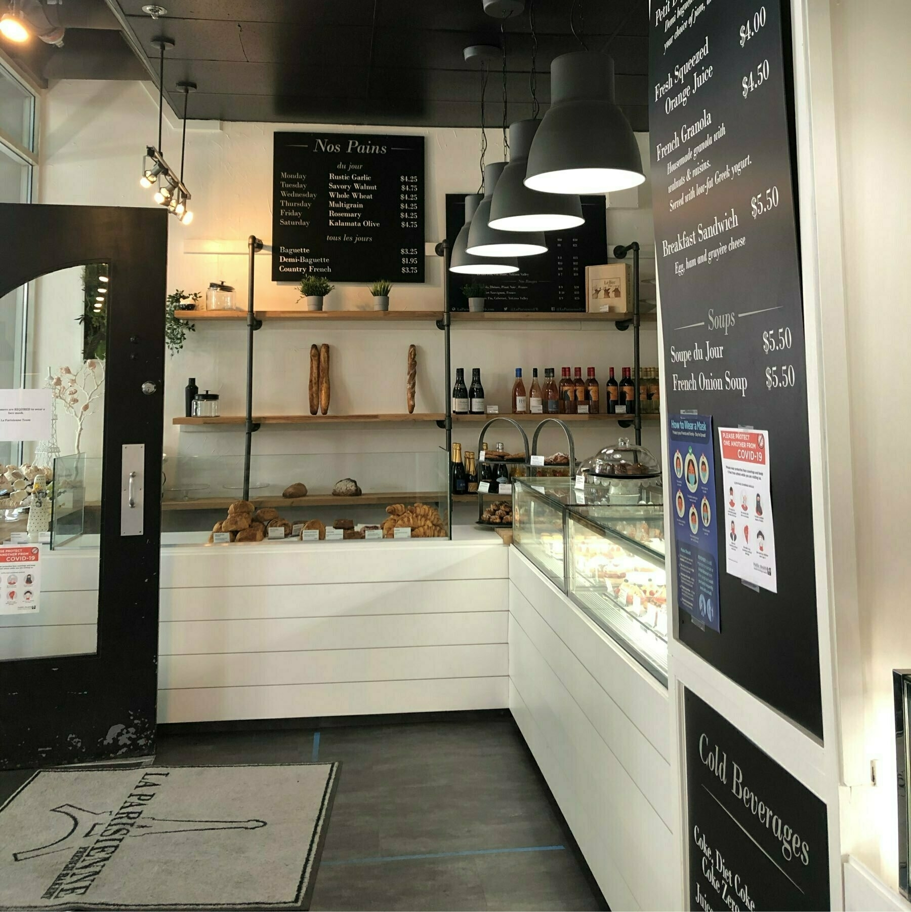 A quaint bakery with glass cases, white walls, and chalkboard signage.