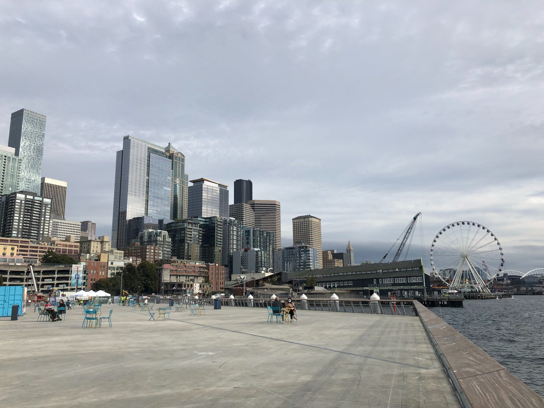 The Seattle skyline is blue and gray against a gray sky. A large concrete pier, very clean and flat is dotted with tables. To the far right, the water of Elliott bay is choppy. The Great Wheel is a round feature in the distance.