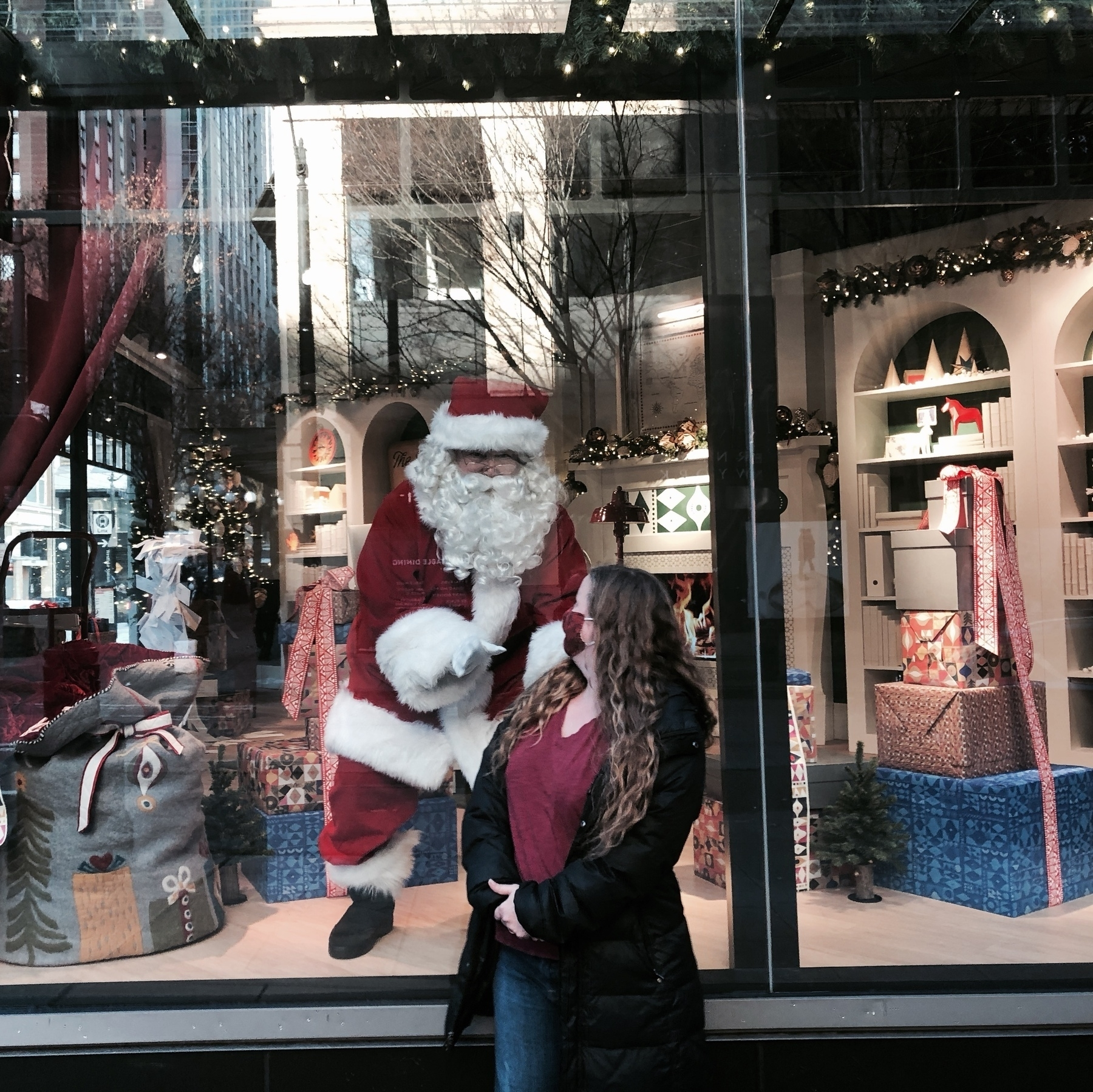 Cheri turns back to look at Santa. He's behind the glass inside a display area at Nordstrom department store