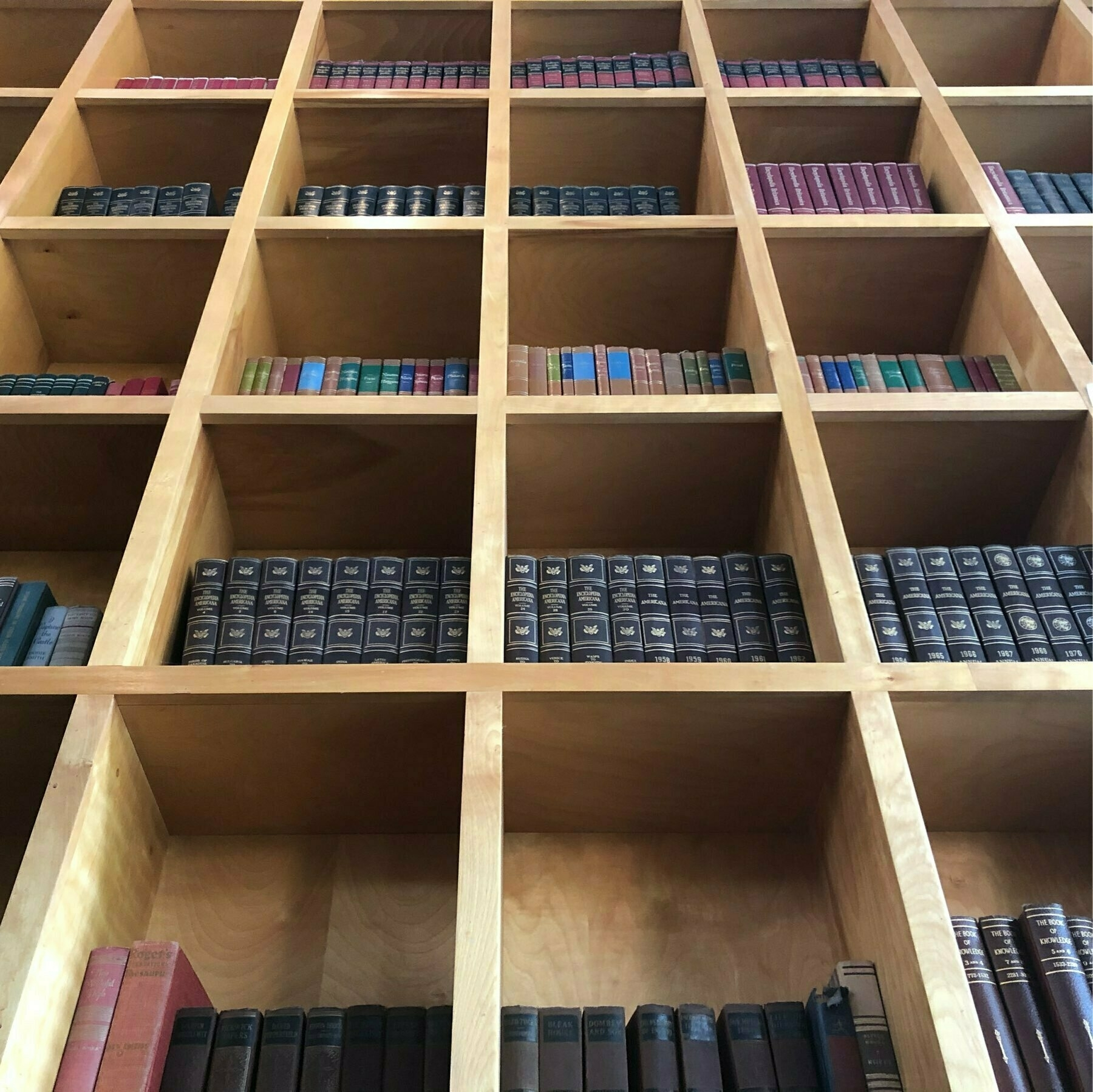 A grid shaped bookcase in light wood. Decorative hardbacks in each square.