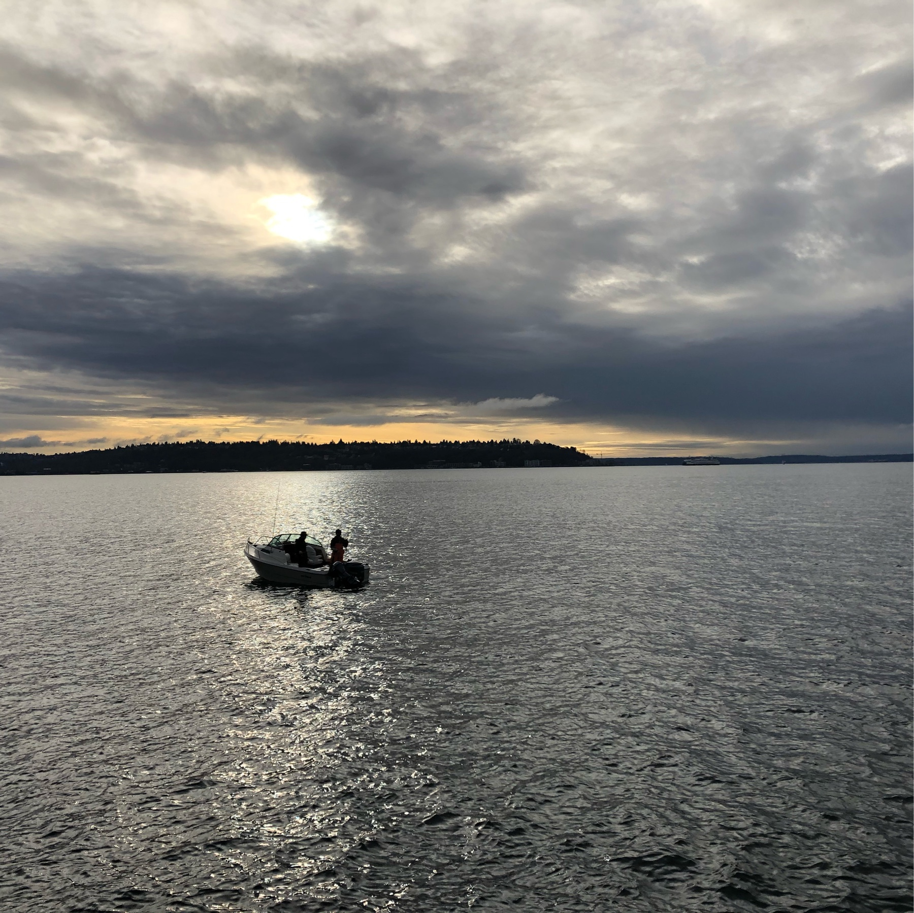 A small fishing boat on pewter colored water, beneath a dramatic cloudy sky.
