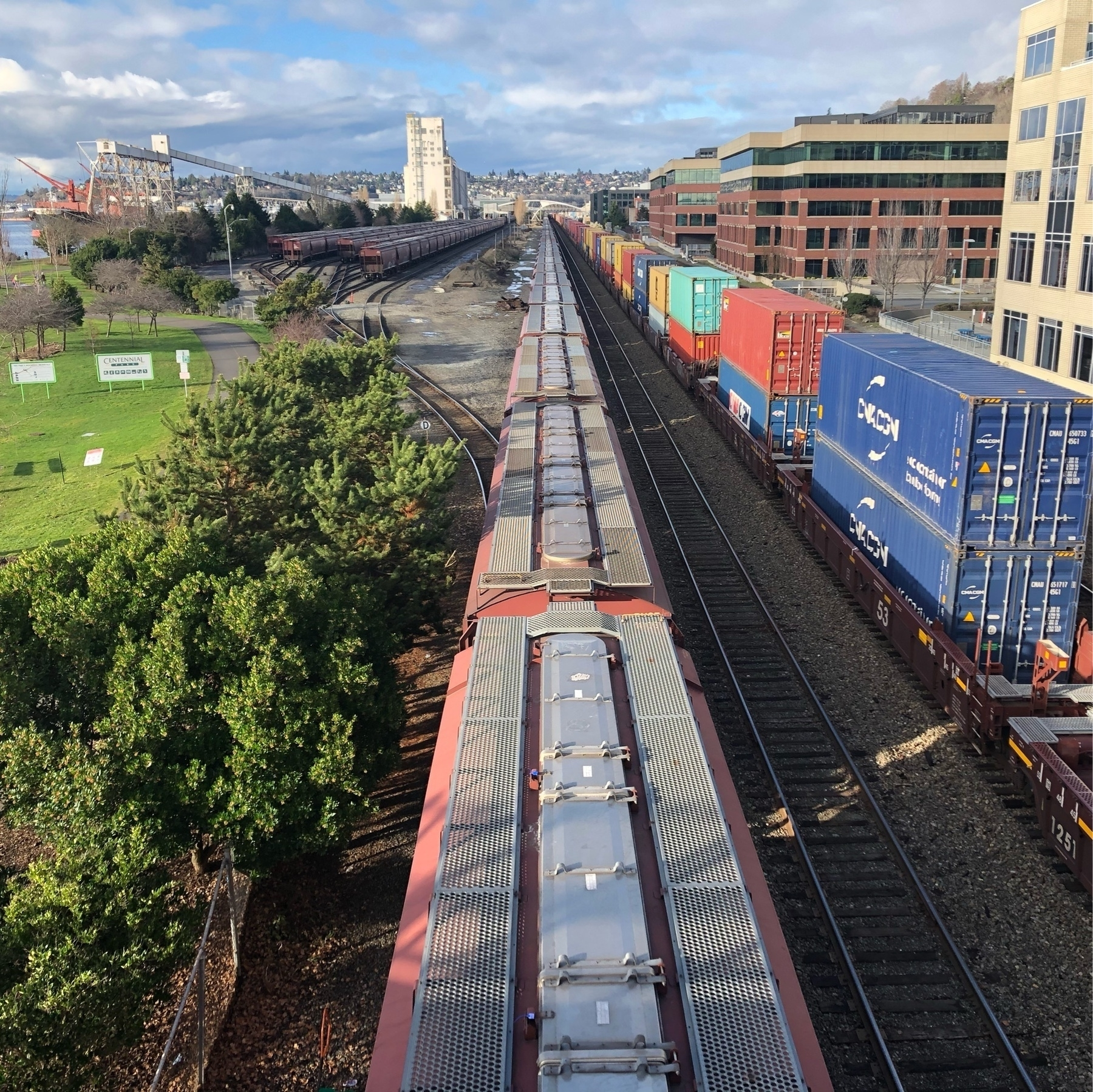 Two cargo trains on the tracks alongside a waterfront park in Seattle.