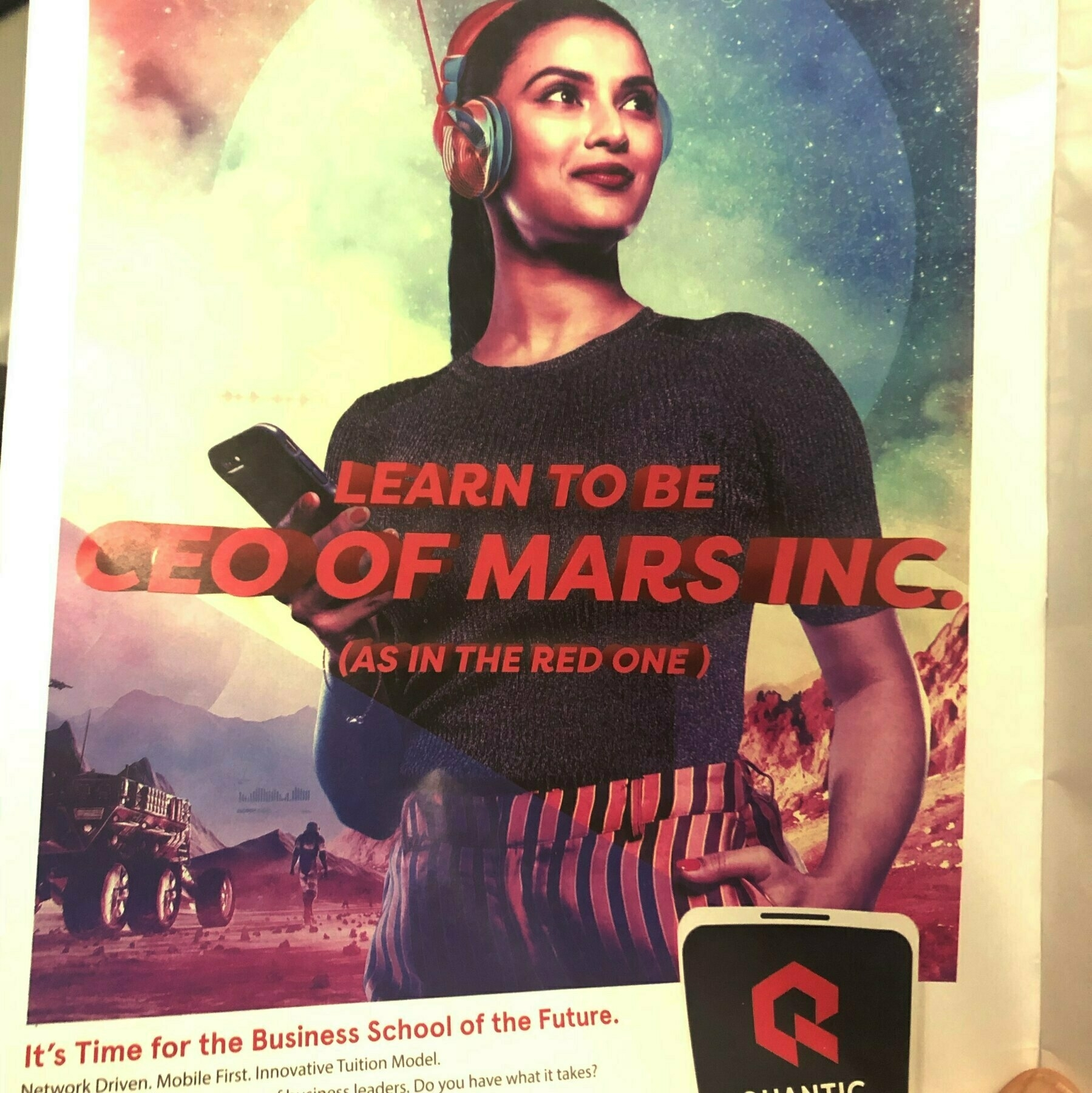"An MBA ad that shows a woman holding up a cell phone. it says ""Learn to be CEO of Mars"" (the Red one)"