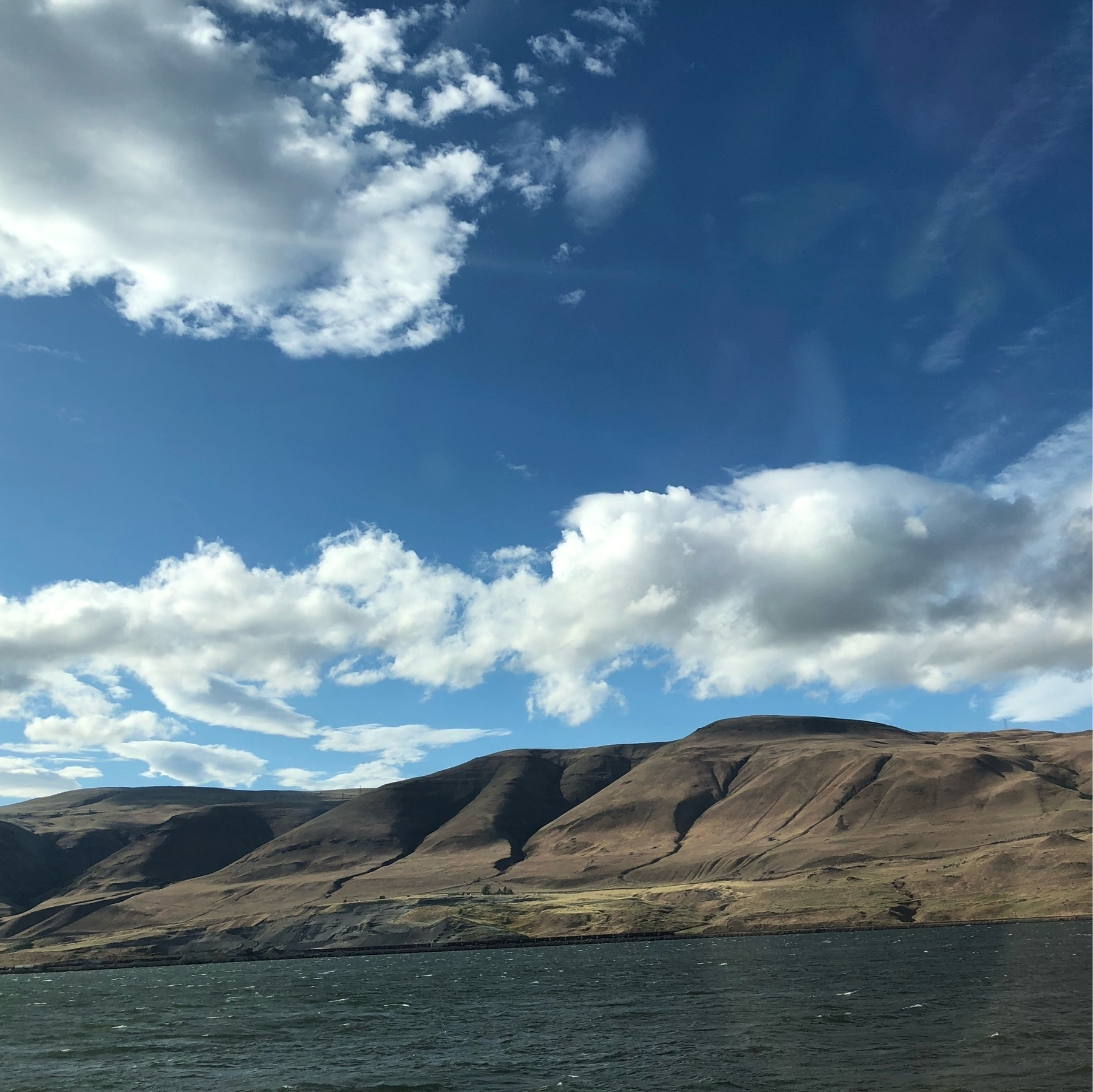 Smooth brown hills roll alongside the slate colored columbia river beneath a cloudy blue sky.