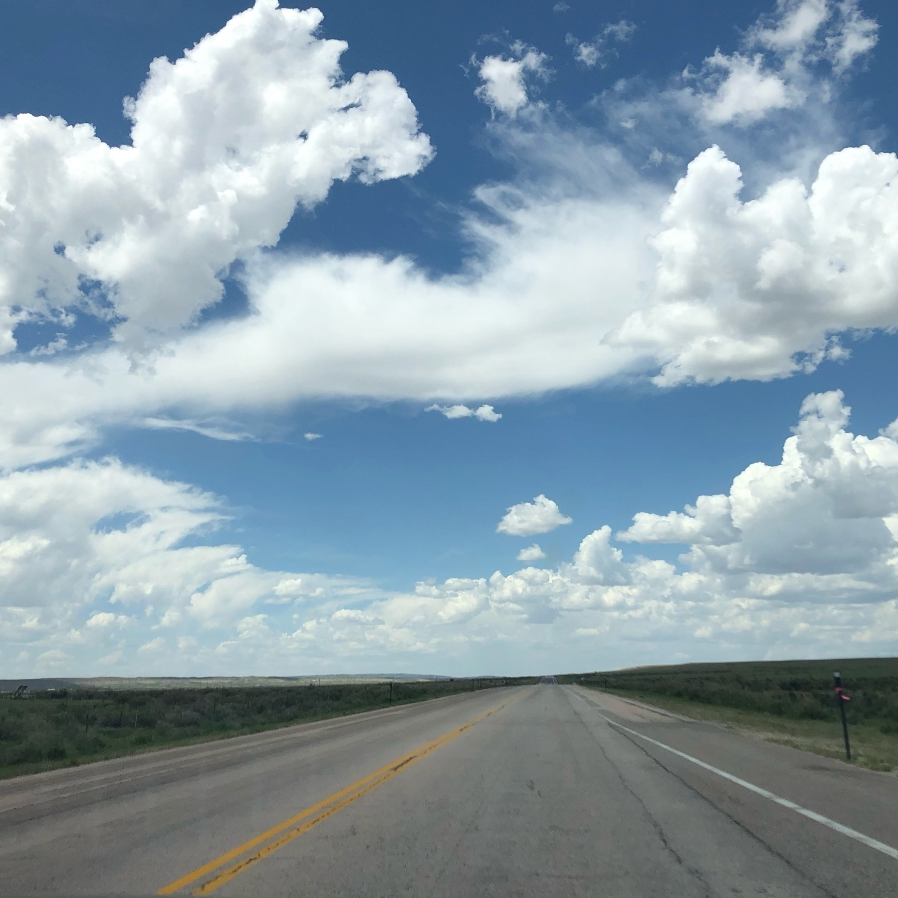 A flat wide freeway with a big blue sky above. Puffy white clouds make the sky look even bigger!