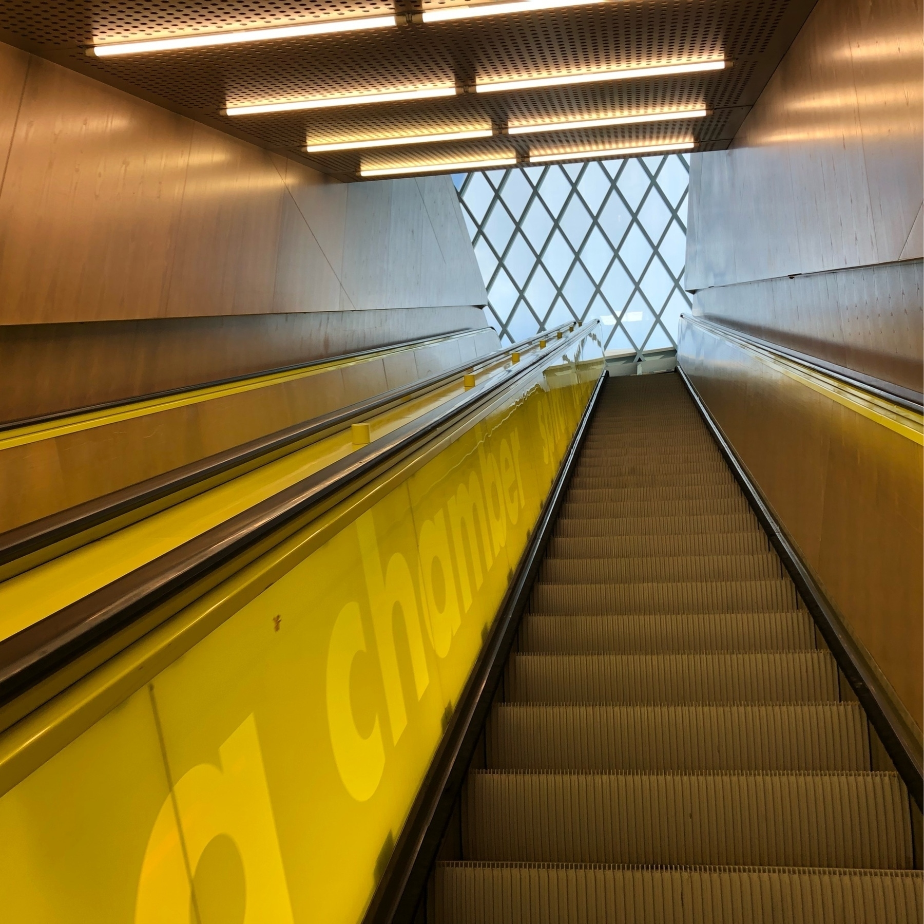 A tall yellow escalator stretches toward a square of glass roof.