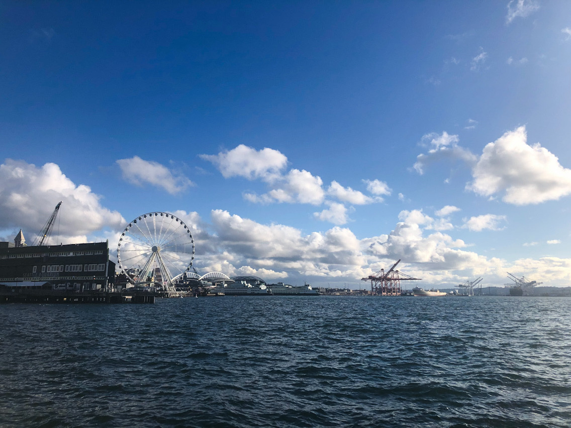 Dark blue ripply waters of Elliott Bay. The Great Wheel (Ferris wheel) and the container shipyards in the distance.