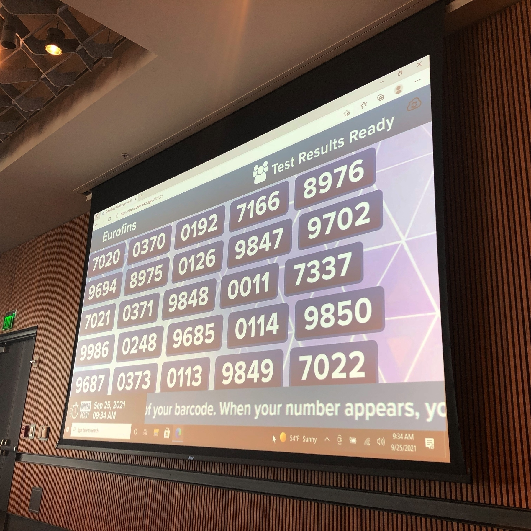 A big wall screen showing four digit numbers. When your number is called your test results are ready.