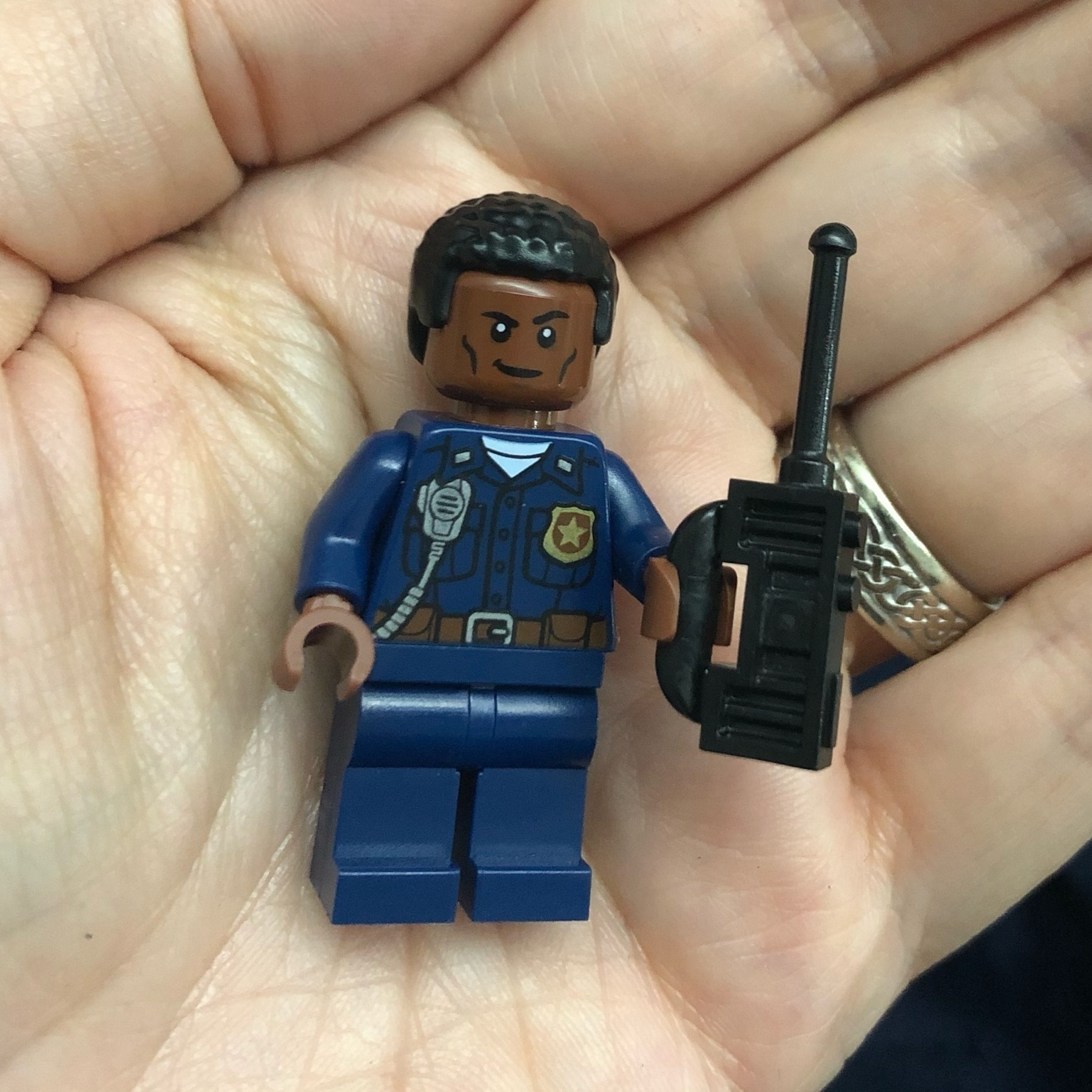 A LEGO minifig of a black policeman. He's holding a walkie talkie
