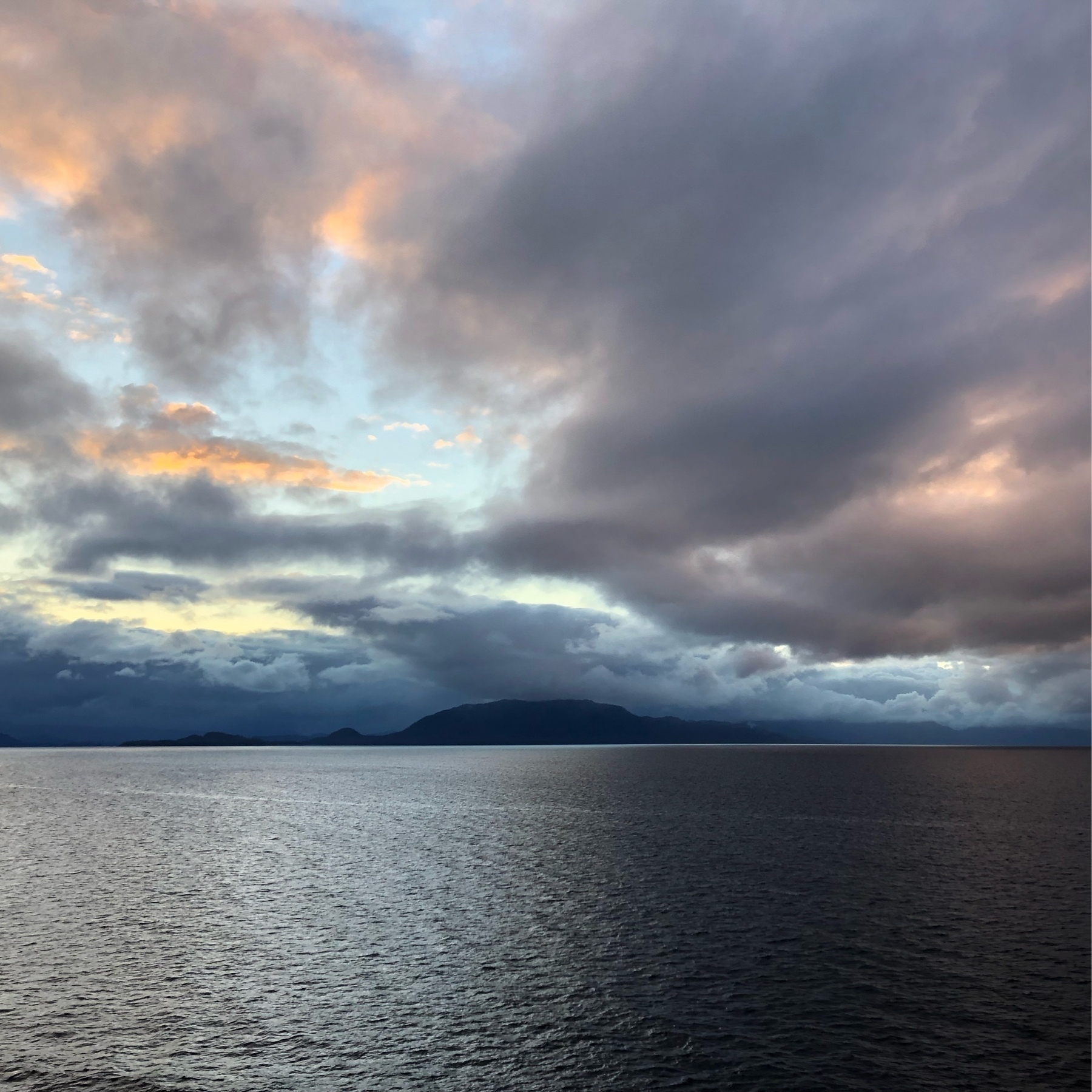 A photo of low hills in the Alaskan Fjords. Silvery blue water, black islands after sunset, and the sky is illumuniated in pale gray, dark gray, and a mere hint of orange. The colors are moody and dark, but the fading sunlight makes the image possible.
