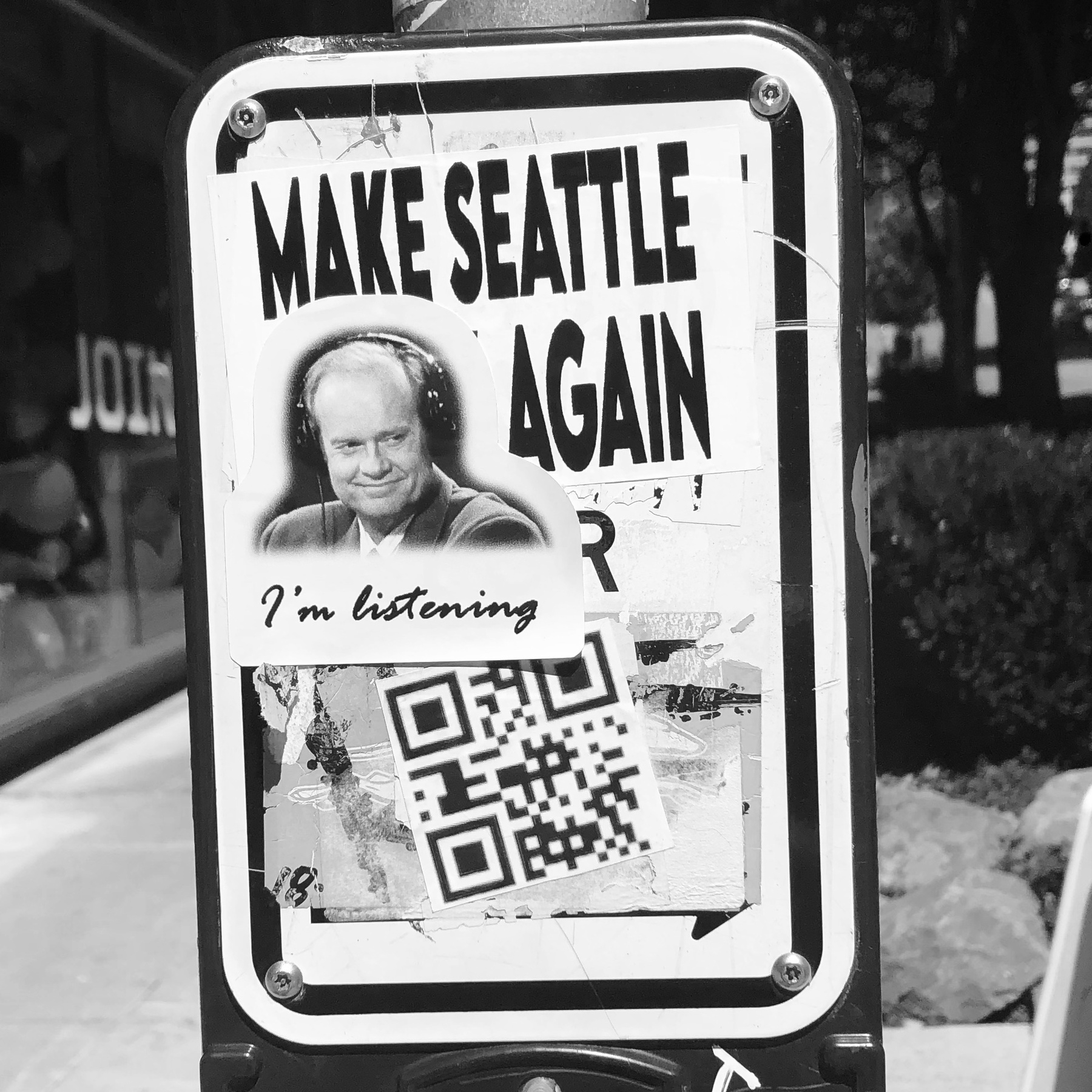 A crosswalk sign covered in graffiti stickers. One is of Frasier Crane and he's saying: I'm listening...