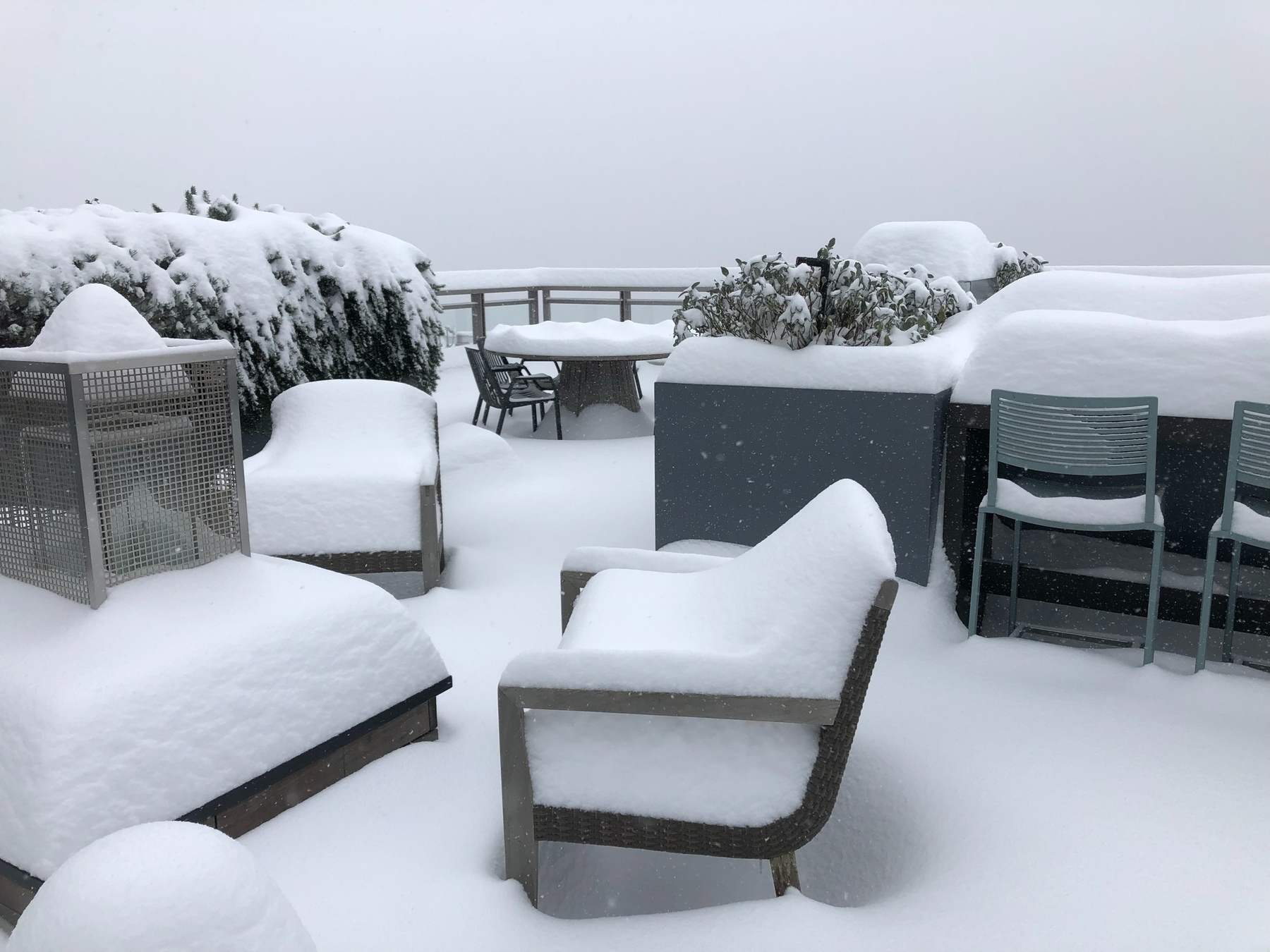 Snow is a foot high atop outdoor furniture  on a downtown rooftop deck.