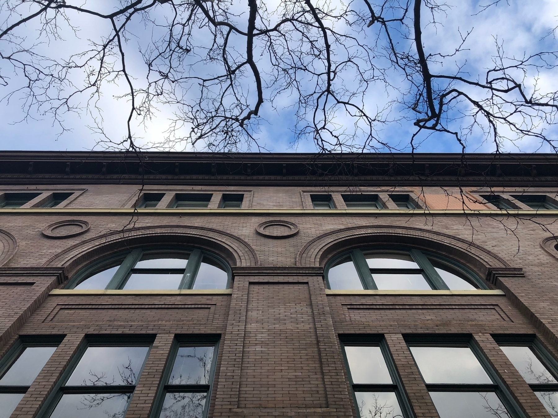 A winter sky peeps above the dramatic arched windows in an old-style brick building.