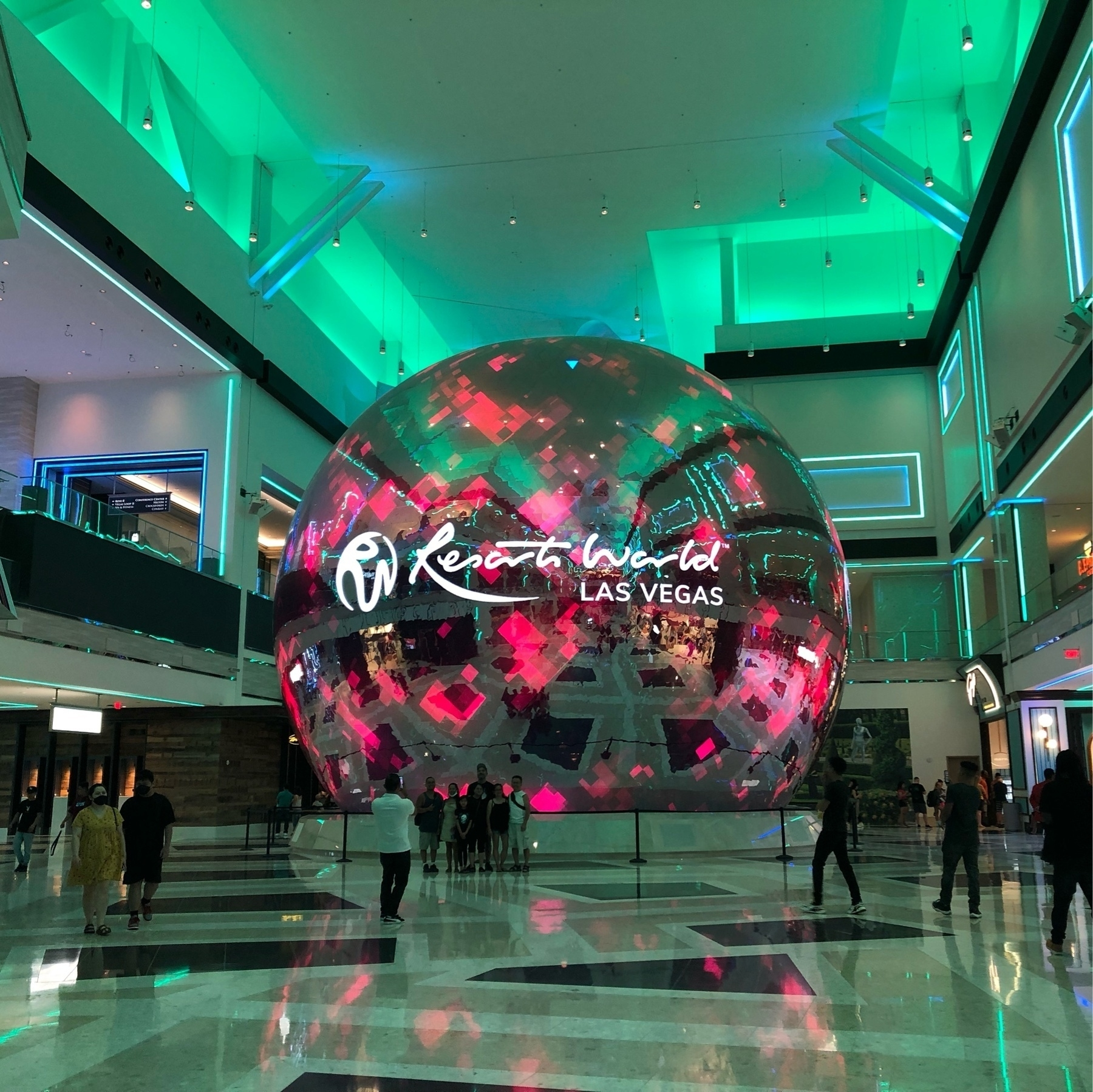 A 40-50 foot reflective sphere in a resort. The room is filled with eerie green light.