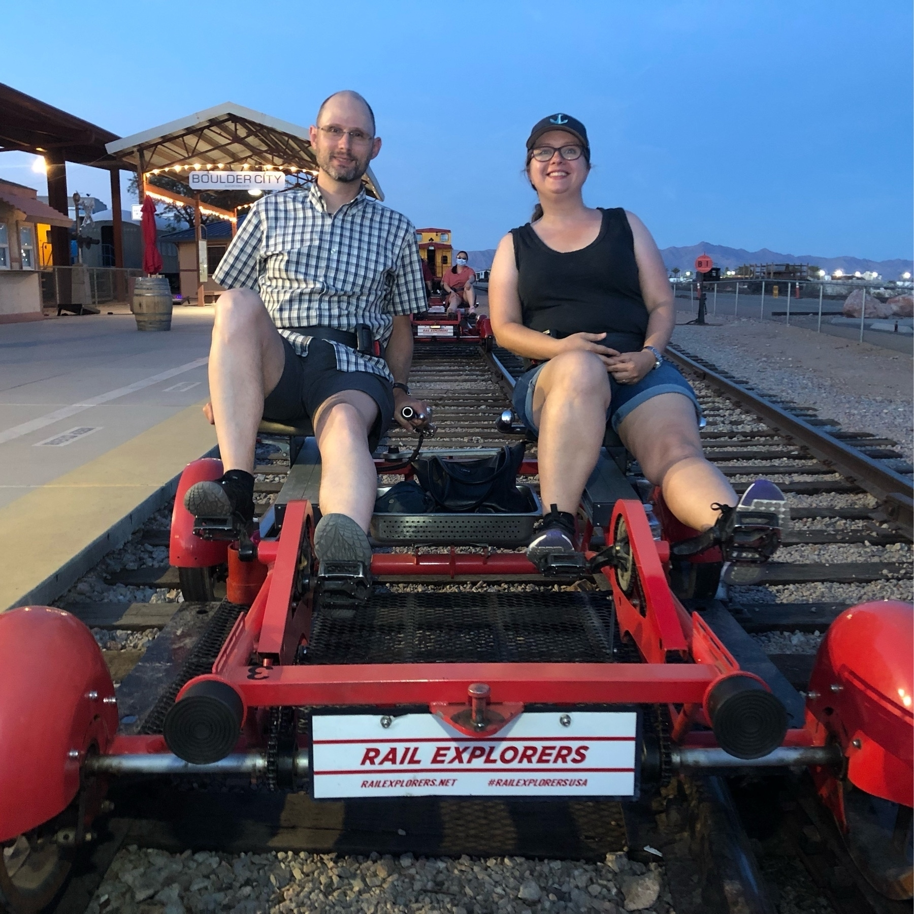Cheri & P sit on a gocart with pedals that's on a rail road track.