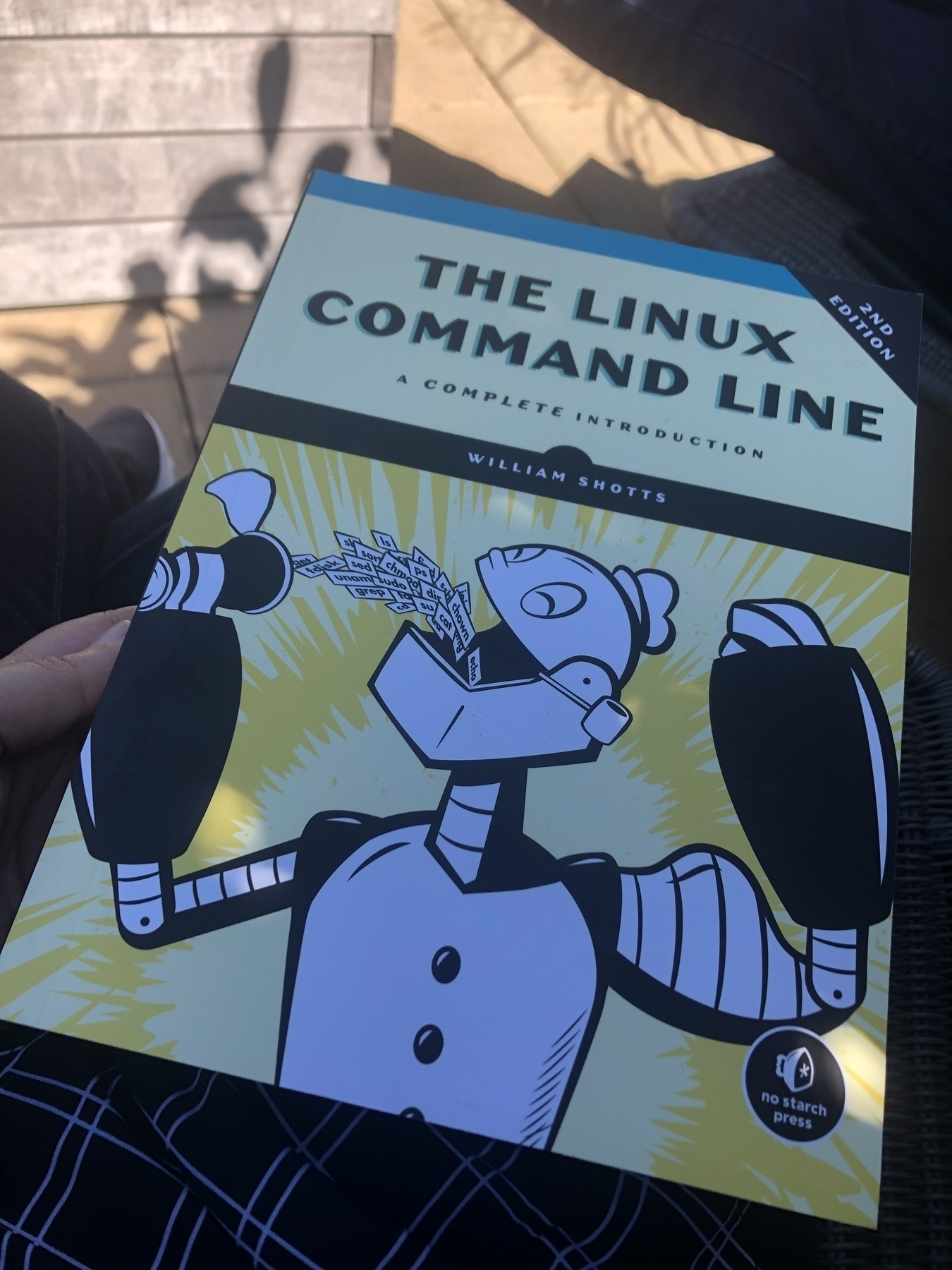 Book cover: An illustration of a robot eating papers with linux commands written on them.