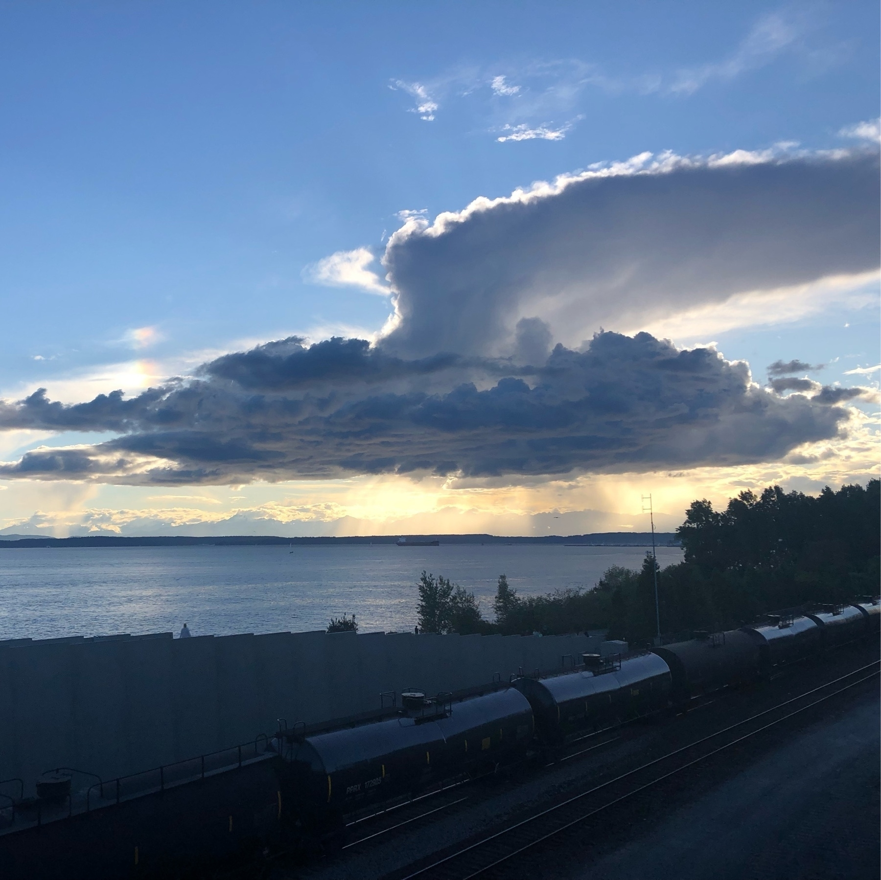 Dramatic silver clouds shaped like an anvil over blue water. An oil train speeds by in the corner of the frame.