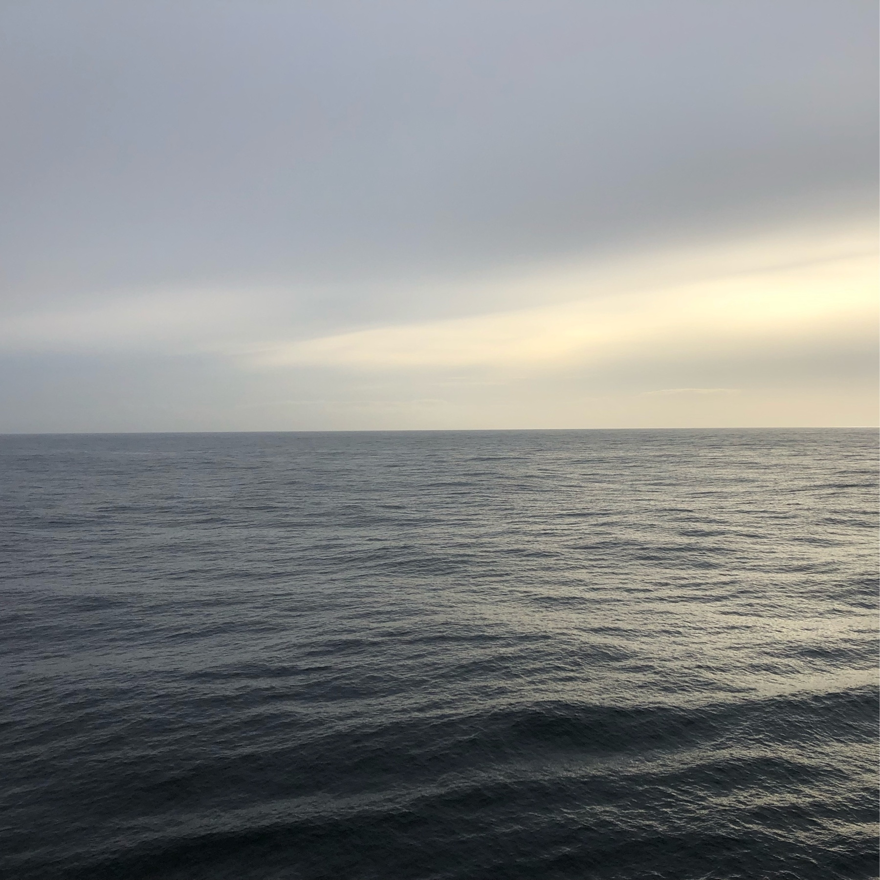 A rather flat pale blue ocean, with a pale gray sky above. Smooth sailing.