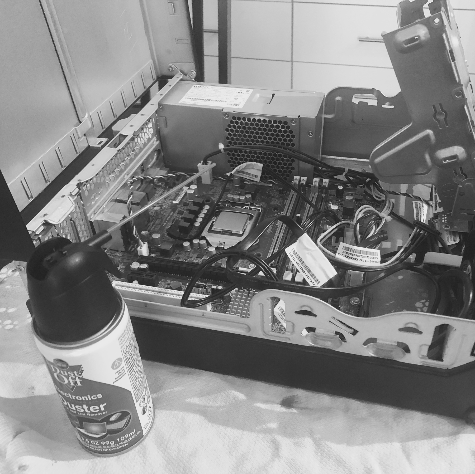 An open desktop PC and a can of compressed air.