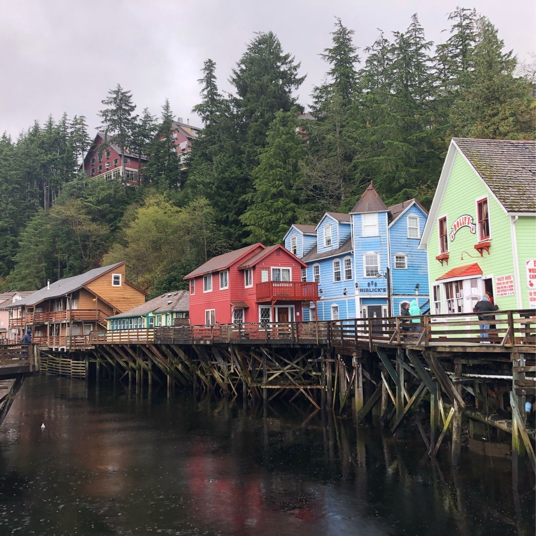 A row of wooden houses perch over a river atop stilts. The houses are brown, yellow, red, green, and blue, creating a colorful rainbow. They're old-timey structures, containing shops in pictureque Ketichikan Alaska.