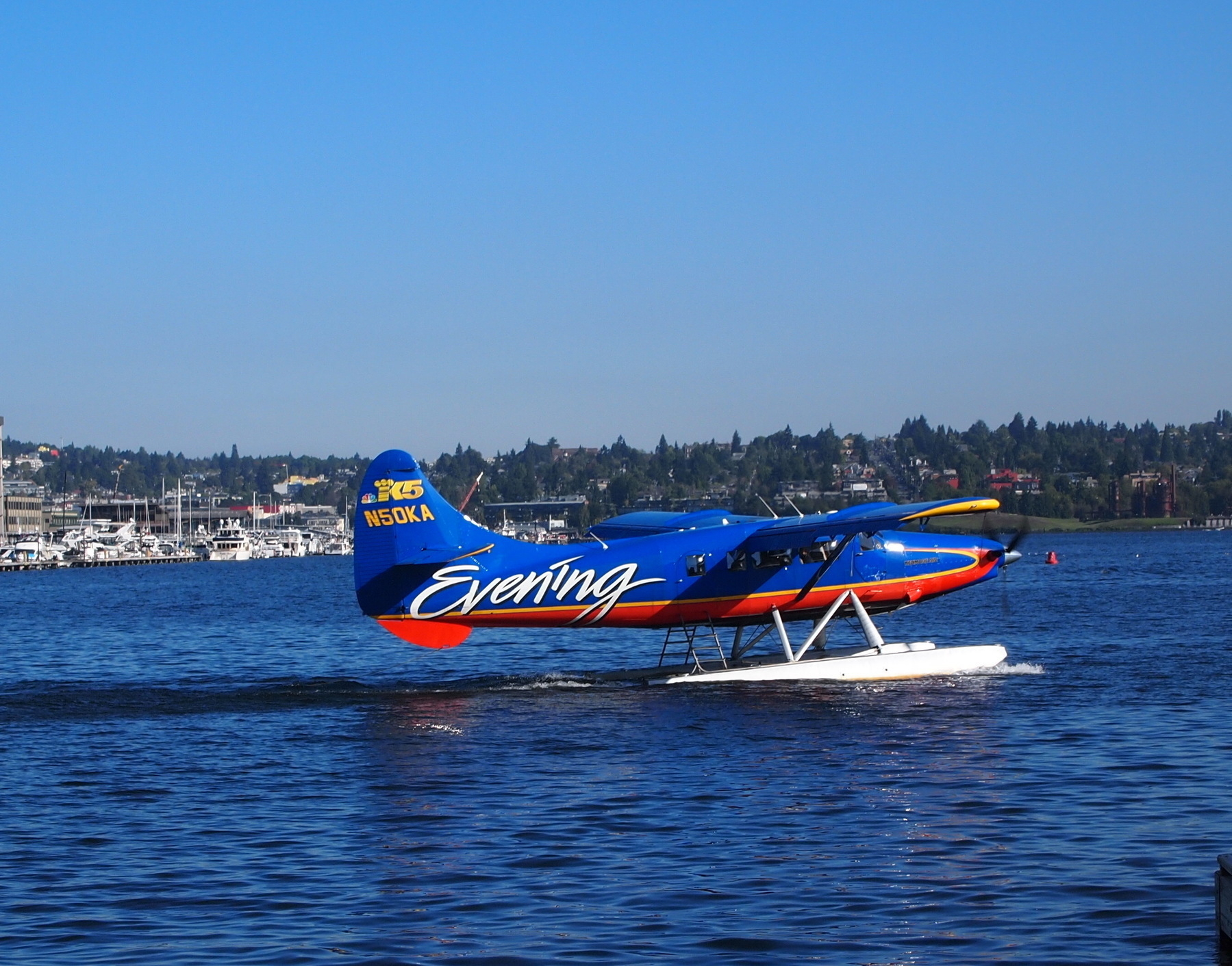 A 10-12 passenger seaplane taxis along the blue water of South Lake Union in Seattle. The plane is painted blue with logos from King 5 news and Evening Magazine, a local television show.