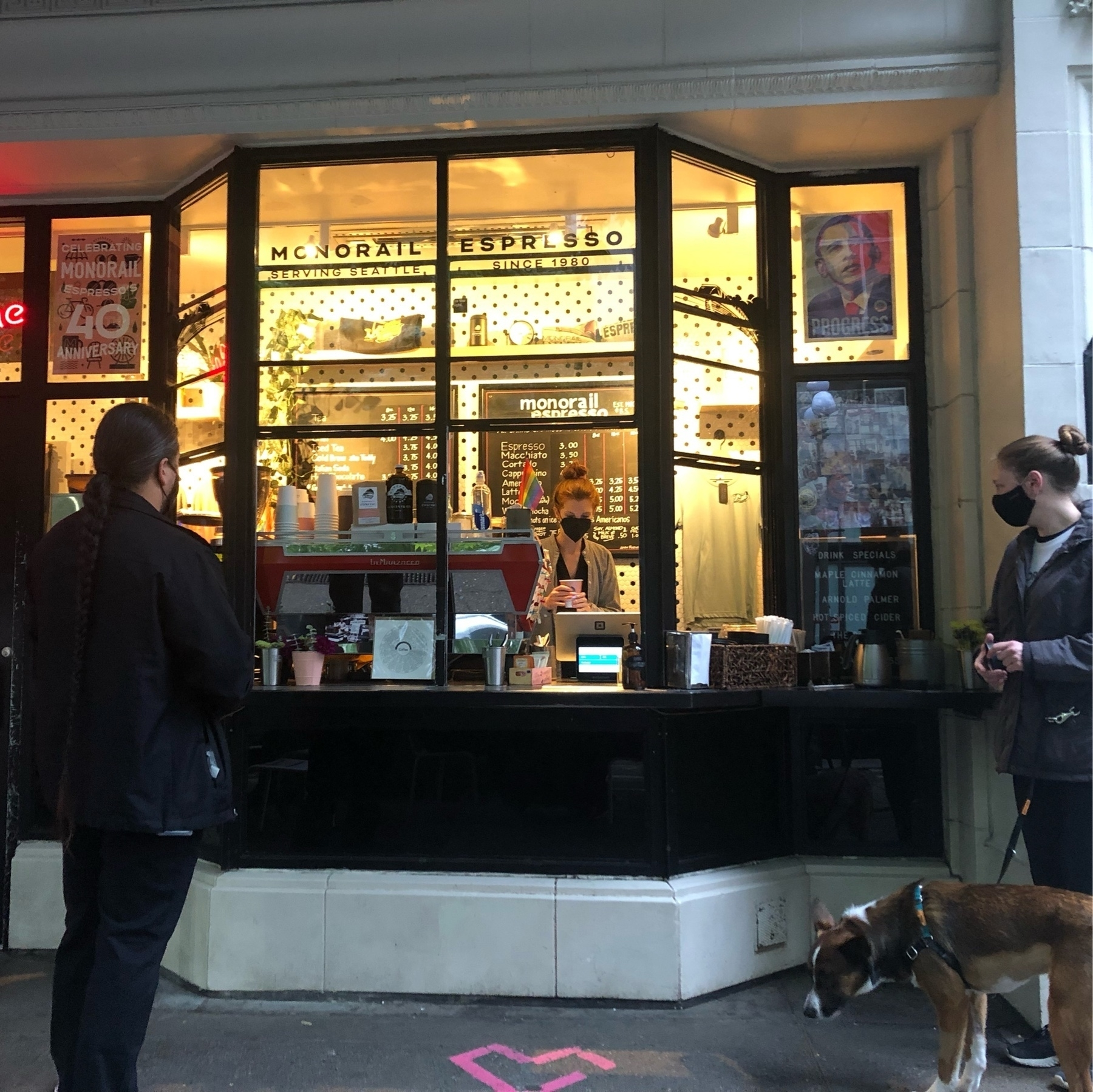 A walk-up coffee window glows yellow in the morning light. Customers wait for caffeine.