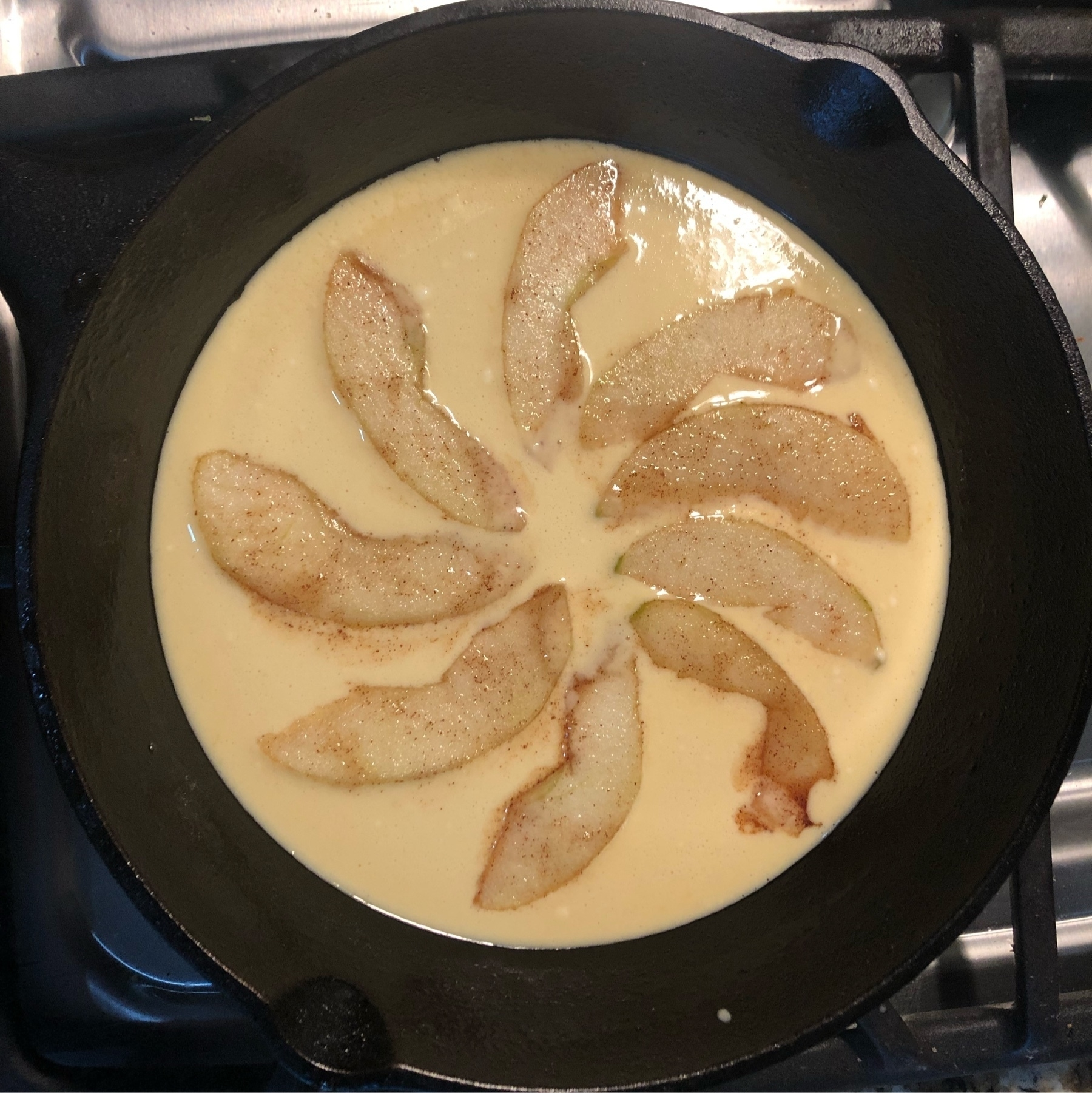 Uncooked pancake batter in a cast iron pan with apple slices fanned out in a flower shape.
