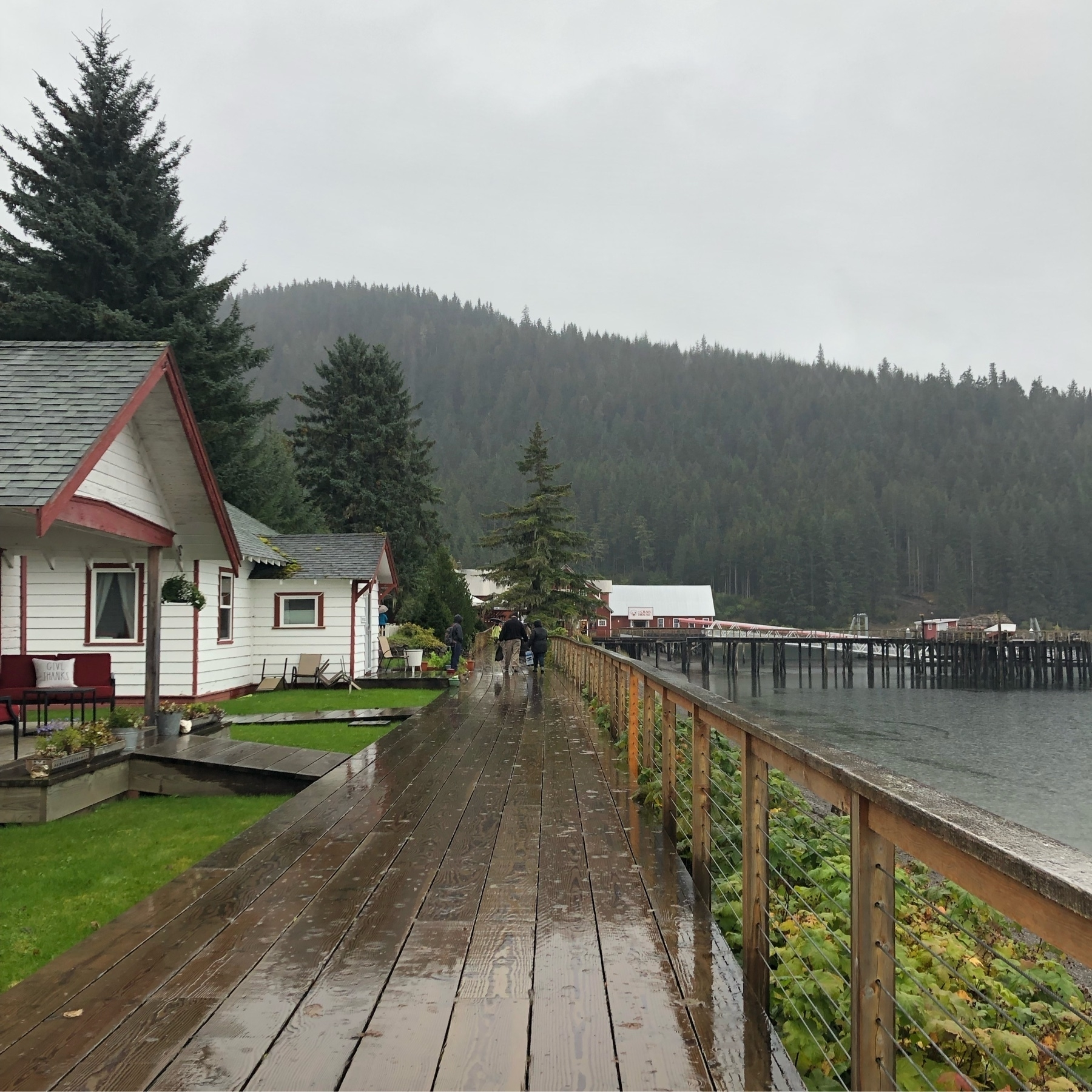 A wet and rainy wooden boardwalk with white bungalows face the water.