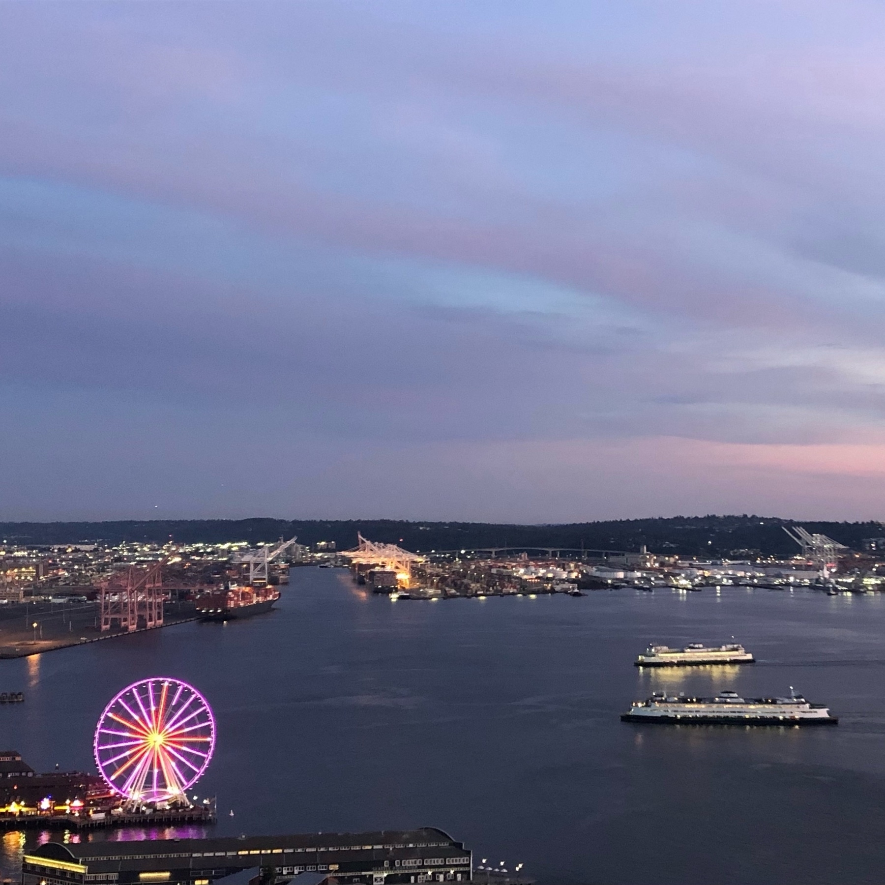 A neon ferris wheel and two long, low ferry boats beneath a pink and blue cloudy sky.