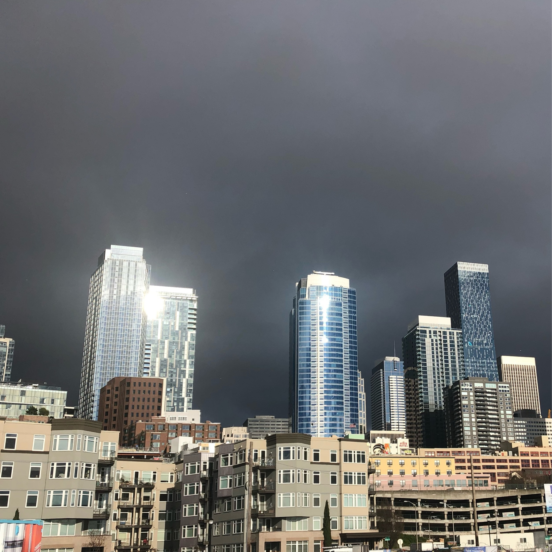 Skyscrapers reflect bright sunlight against a bank of dark and impenetrable clouds