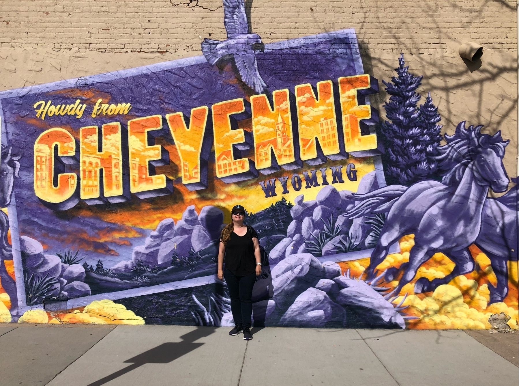 Cheri stands in front of a Welcome to Cheyenne mural painted like a postcard. Purple with wild horses.
