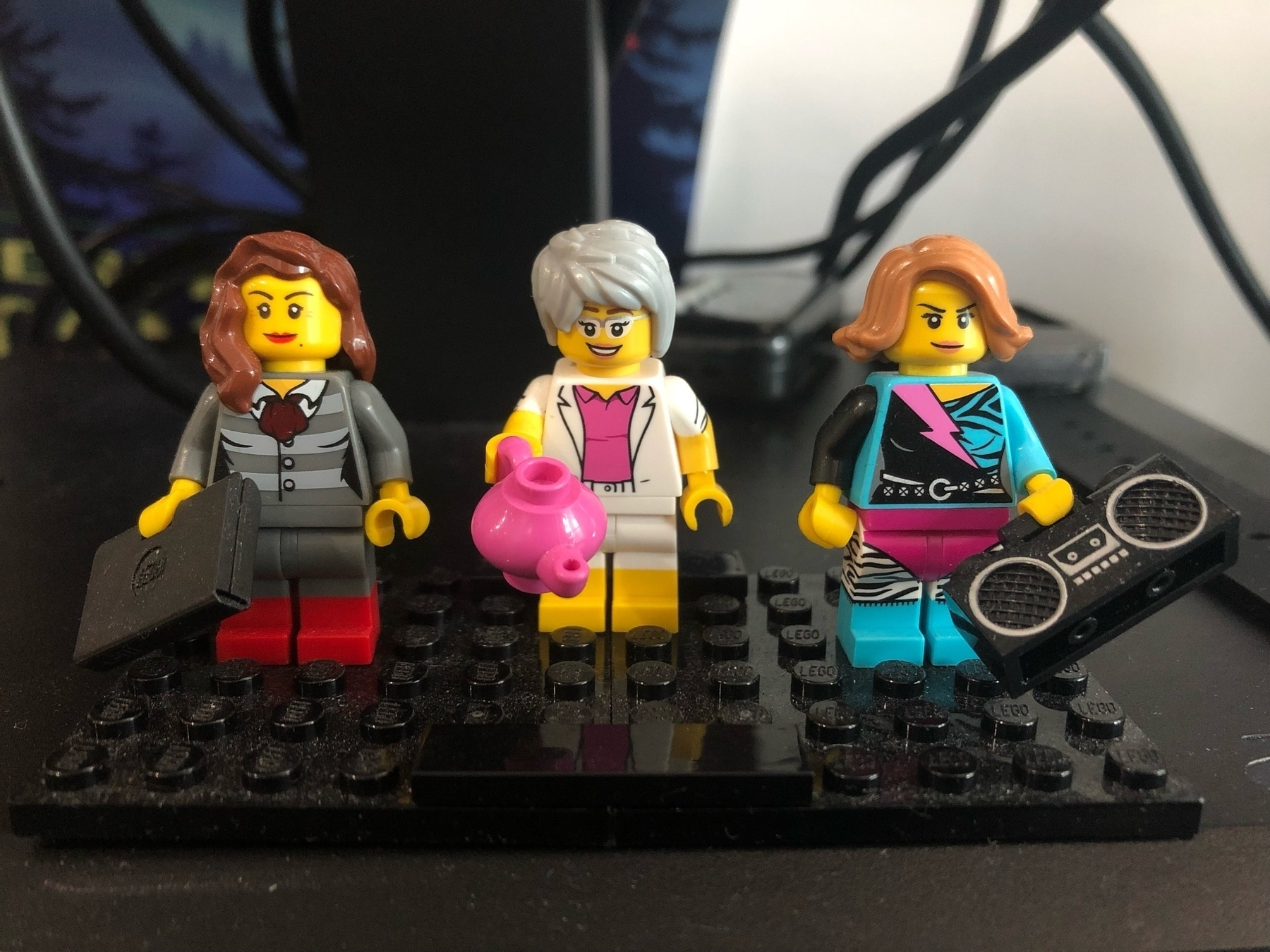 Three LEGO minifigs. A brunette in a suit, a gray haired woman holding a tea pot, A light haired brunette in colorful 80s workout gear.
