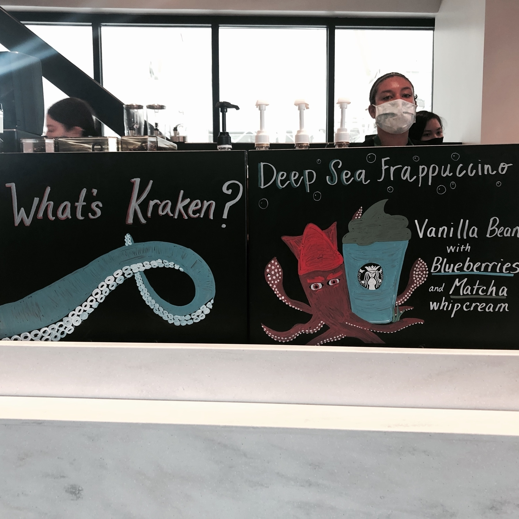 """A starbucks chalkboard asking """"whats Kracken?"""" with a blueberry-macha Frappucino described. The drink is in blue and red Kraken colors."""