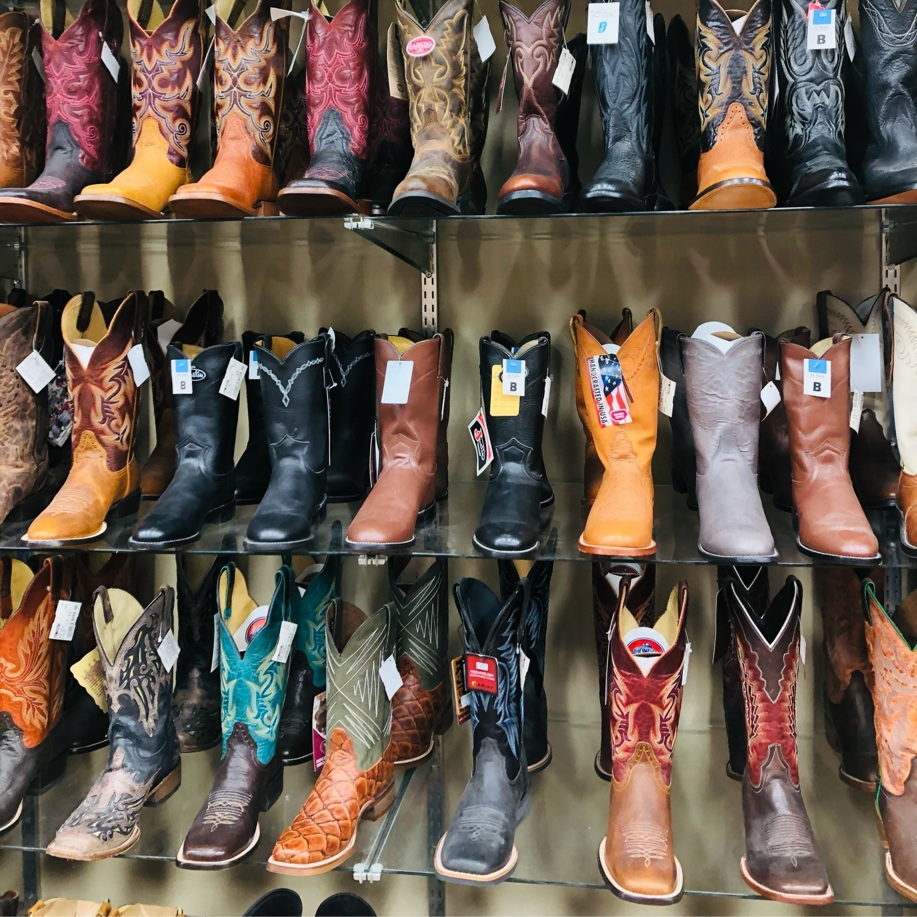 A wall rack full of colorful western boots. So many colors and varieties!