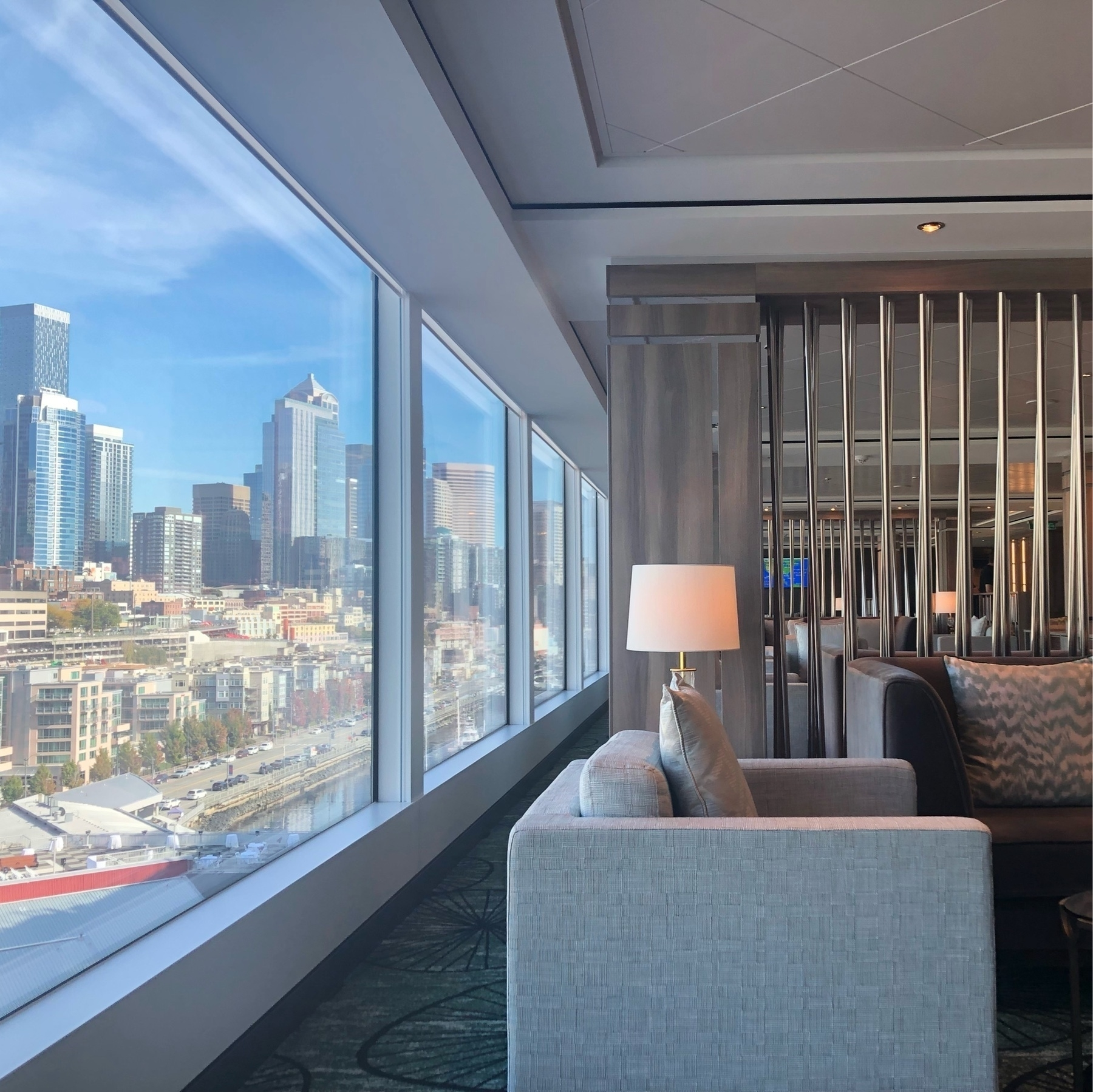 A fancy lounge with modern decor and square couches. To the left, downtown Seattle is visible through the big windows. The day is sunny.