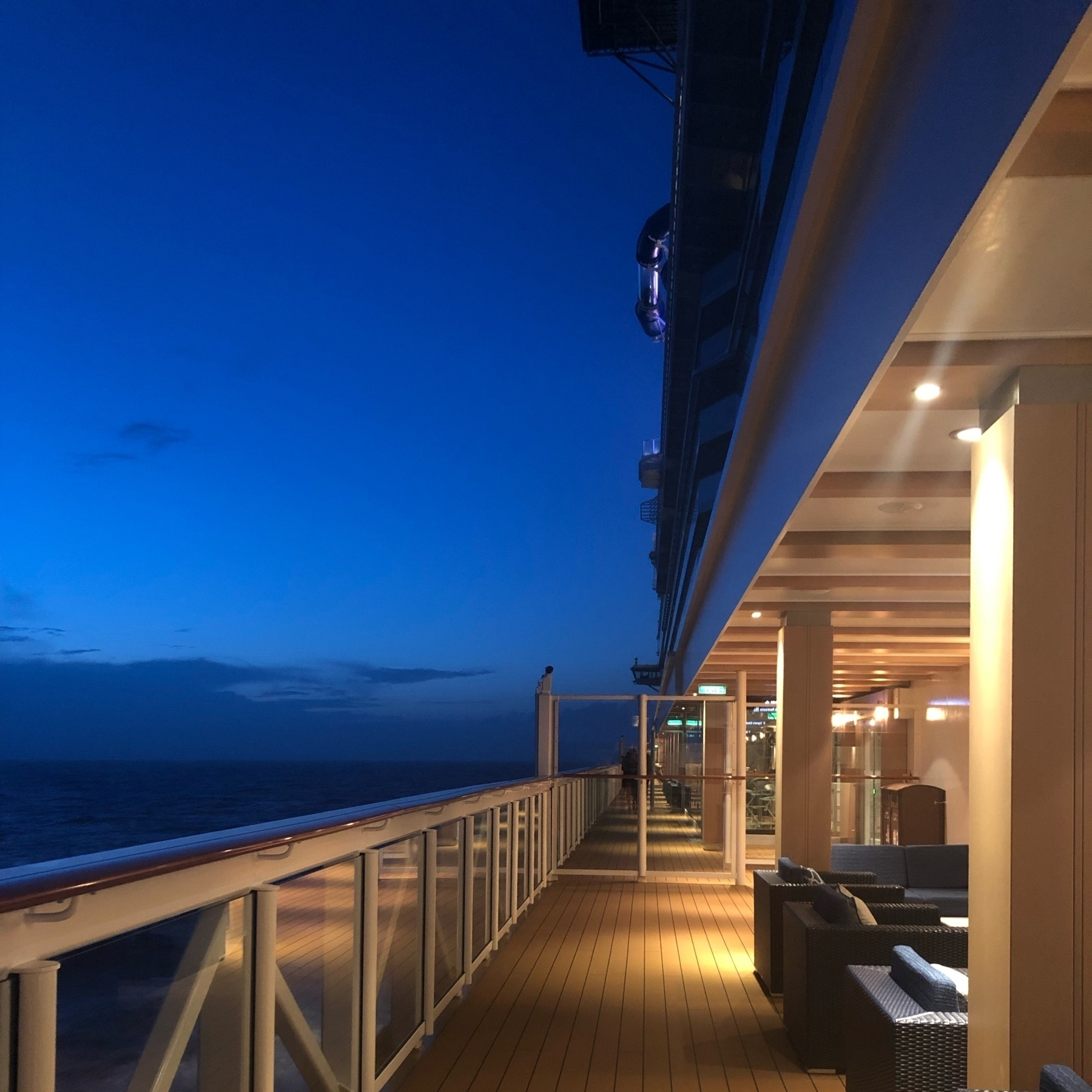 Azure blue light surrounds a cruise ship at fusk. The light of the promenade deck is golden yellow, the walking path shoots straight forward, to the left, the rail and water.