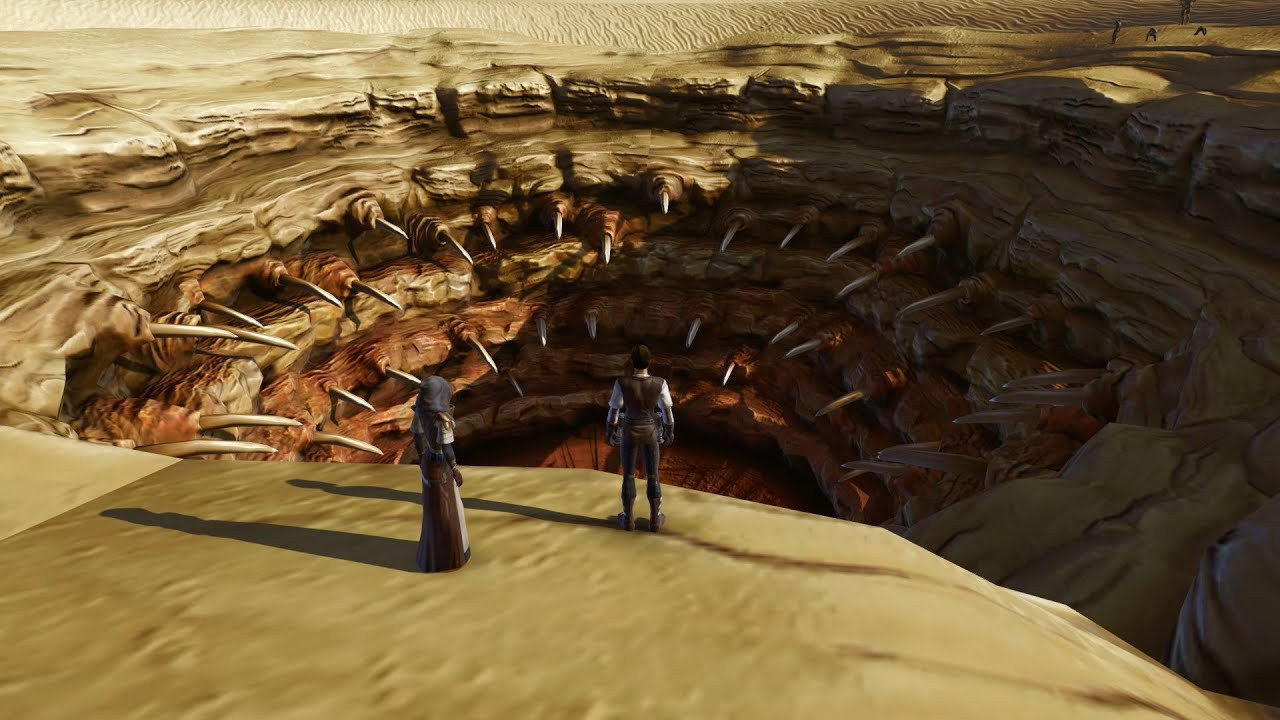 A still of two figures standing nex to the Star Wars Sarlac pit: A gaping toothed mouth in the desert large enough to swallow a house.
