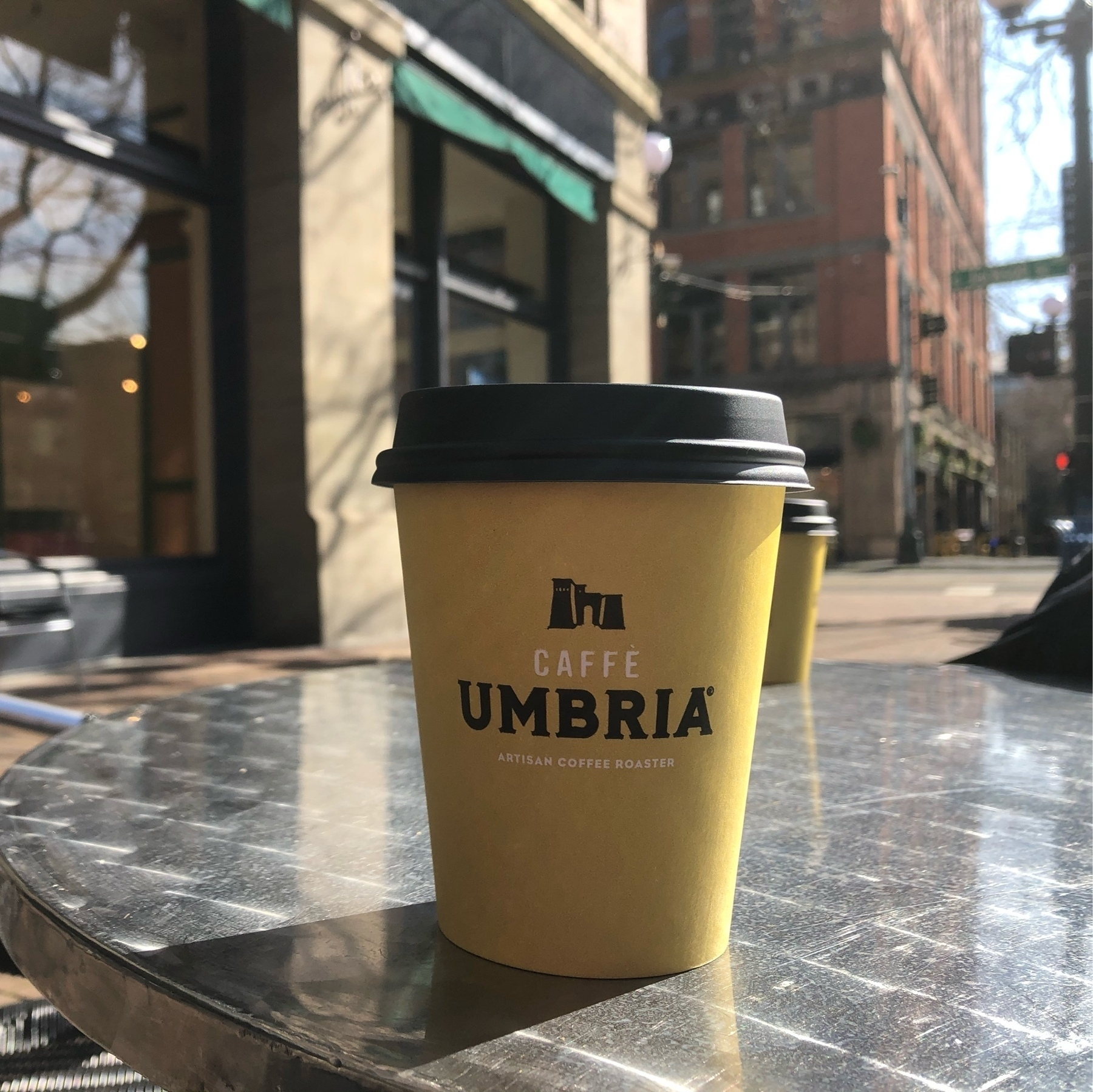 A yellow coffee cup on an aluminum table