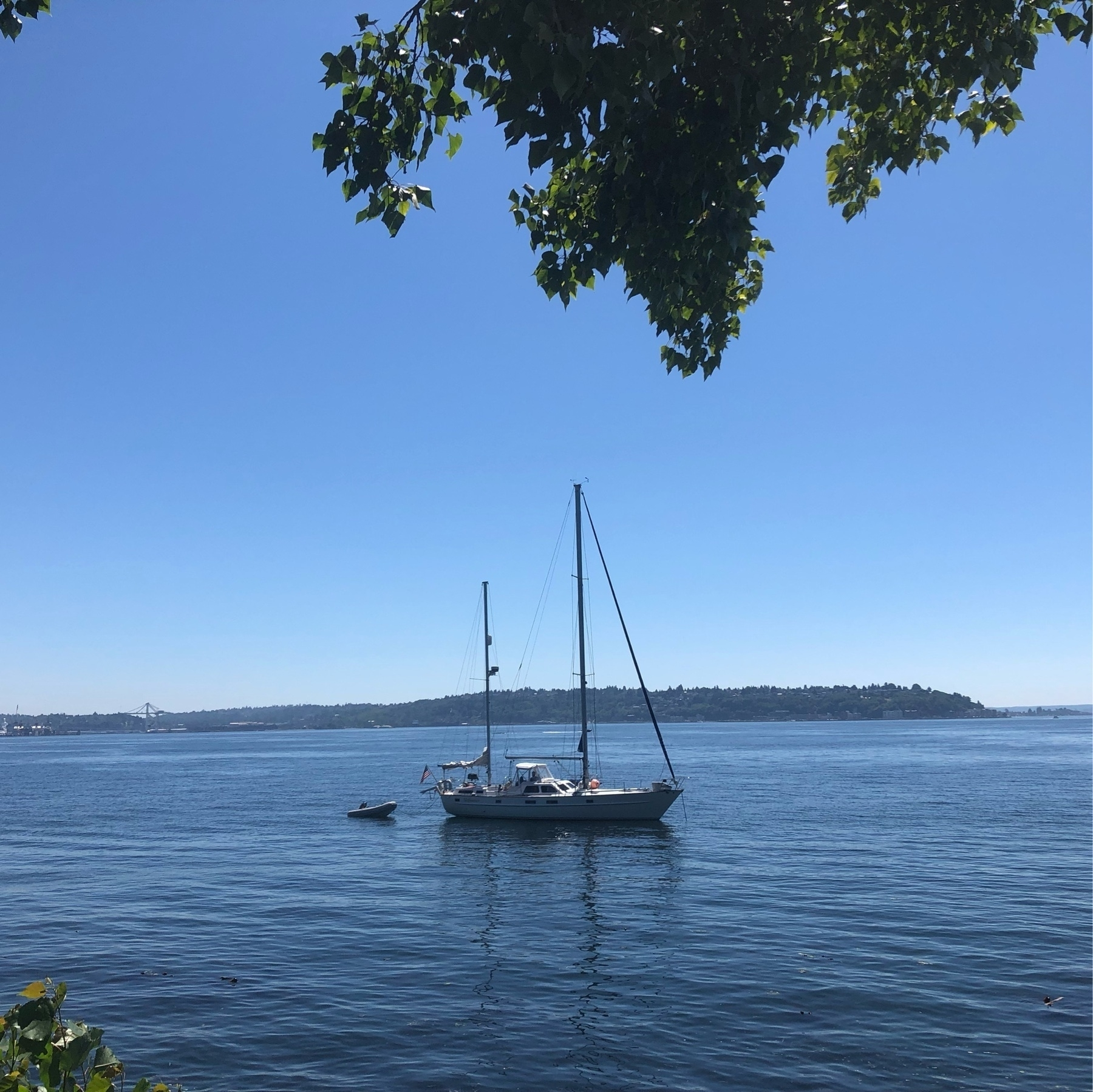 A sailboat rests just offshore with it's sail down.