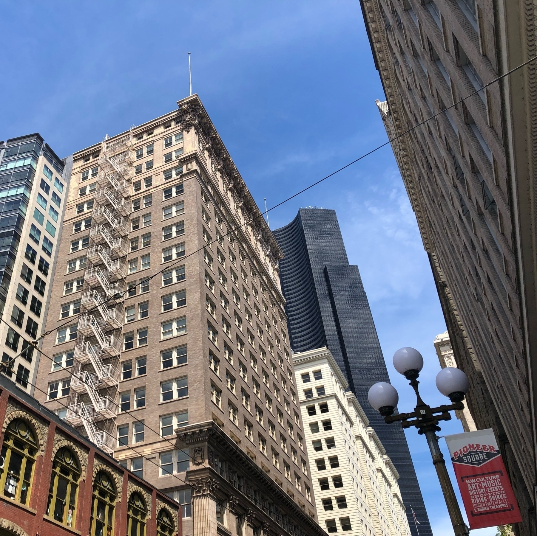 An assortment of city buildings, old and new, glass and brick. One tall brick building has a fire escape zig-zagging up the side.