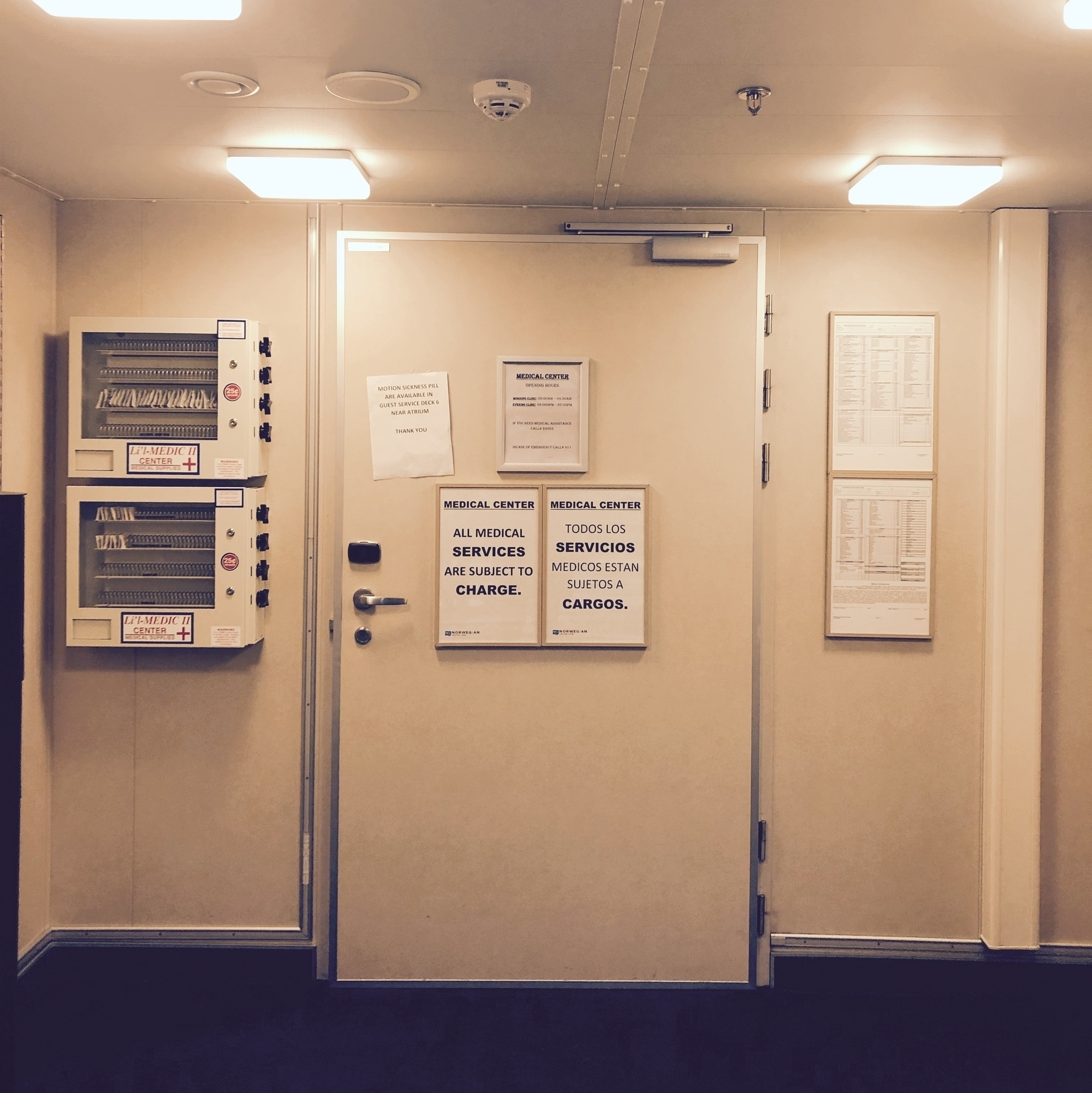 A yellowish photo of a cruise ship's medical center door. Signs indicate that services will incur a fee. Signs are in English and Spanish.