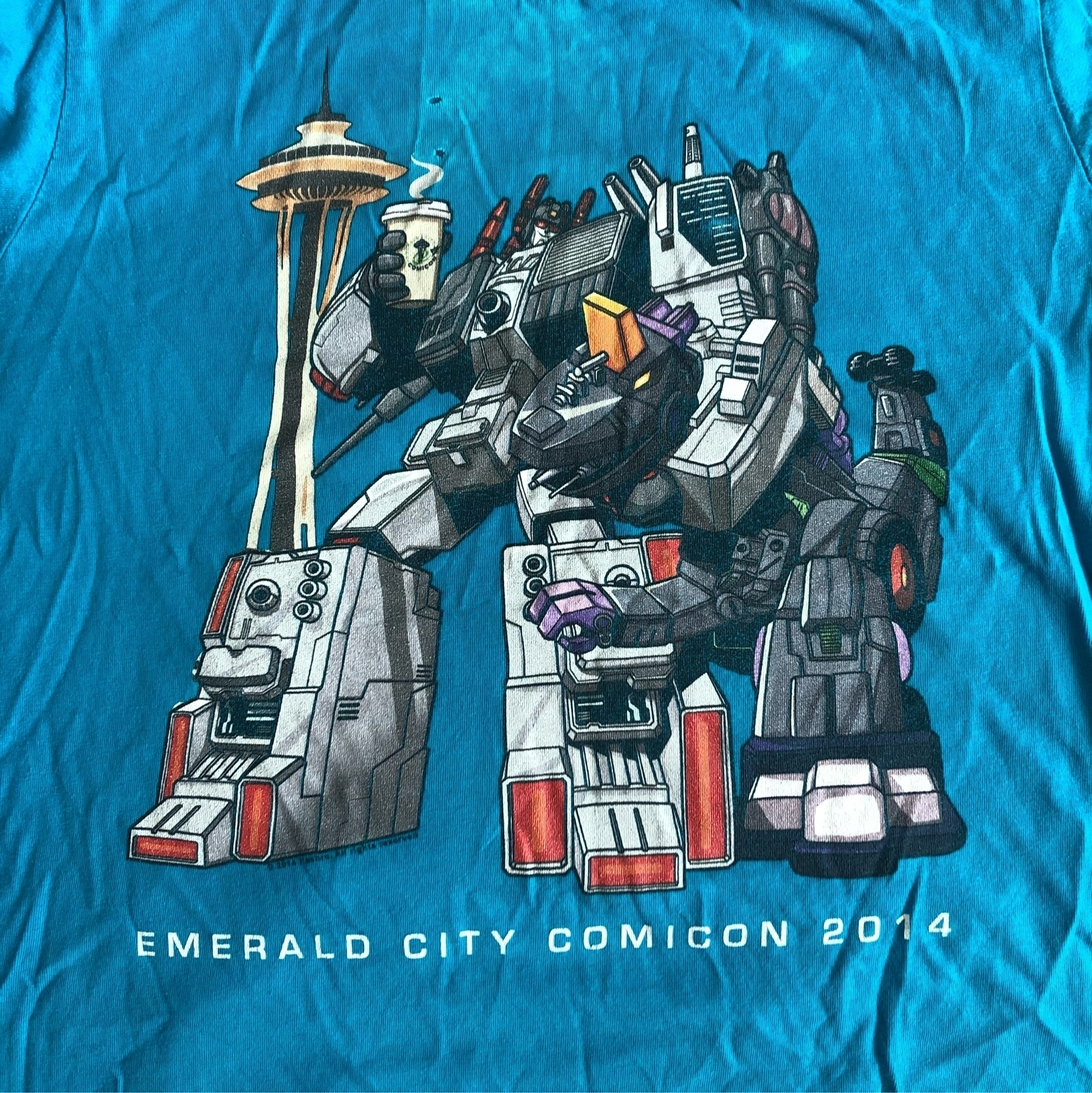 A worn out 2014 Emerald City Comicon Tee with Star Scream next to the space Needle