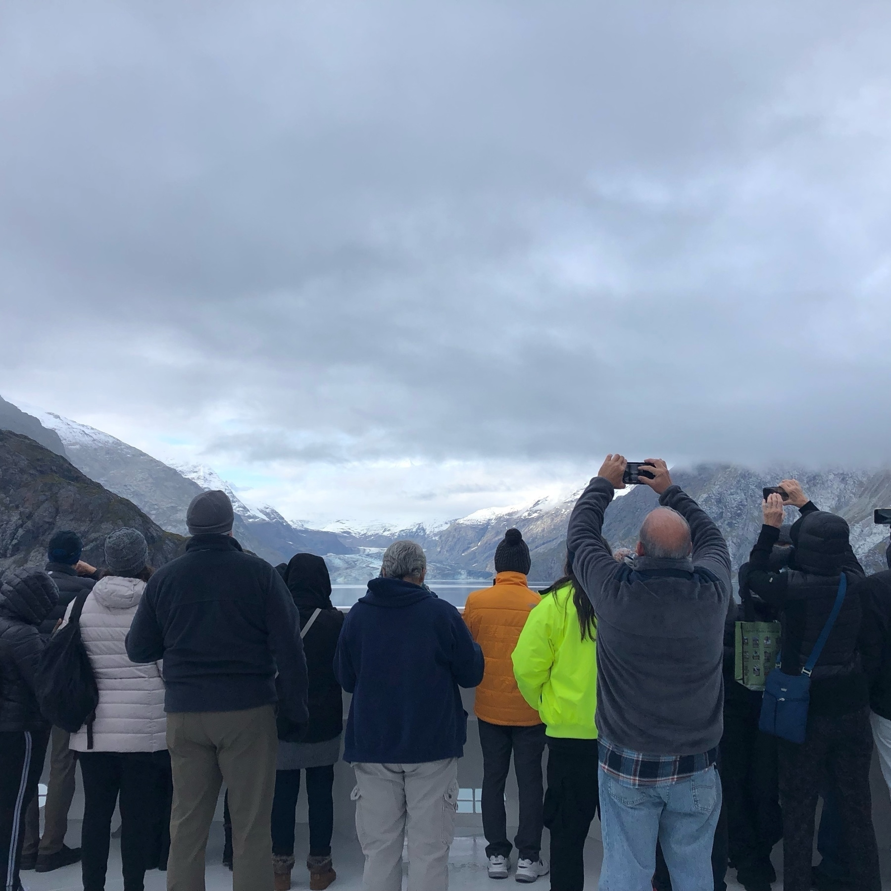 A dozen middle-aged cruise passengers in winter coats and hats hold up phones and cameras as the bow of the ship approaches a watery inlet. Tall frosty mountains in the distance add an element of adventure.