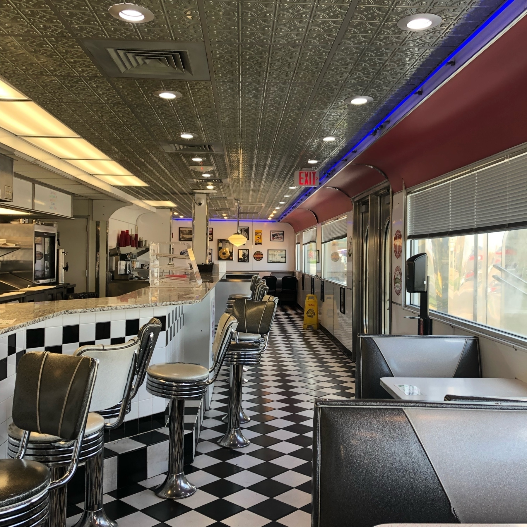An old fashioned diner with a checkered floor, round stools, and a tin ceiling.